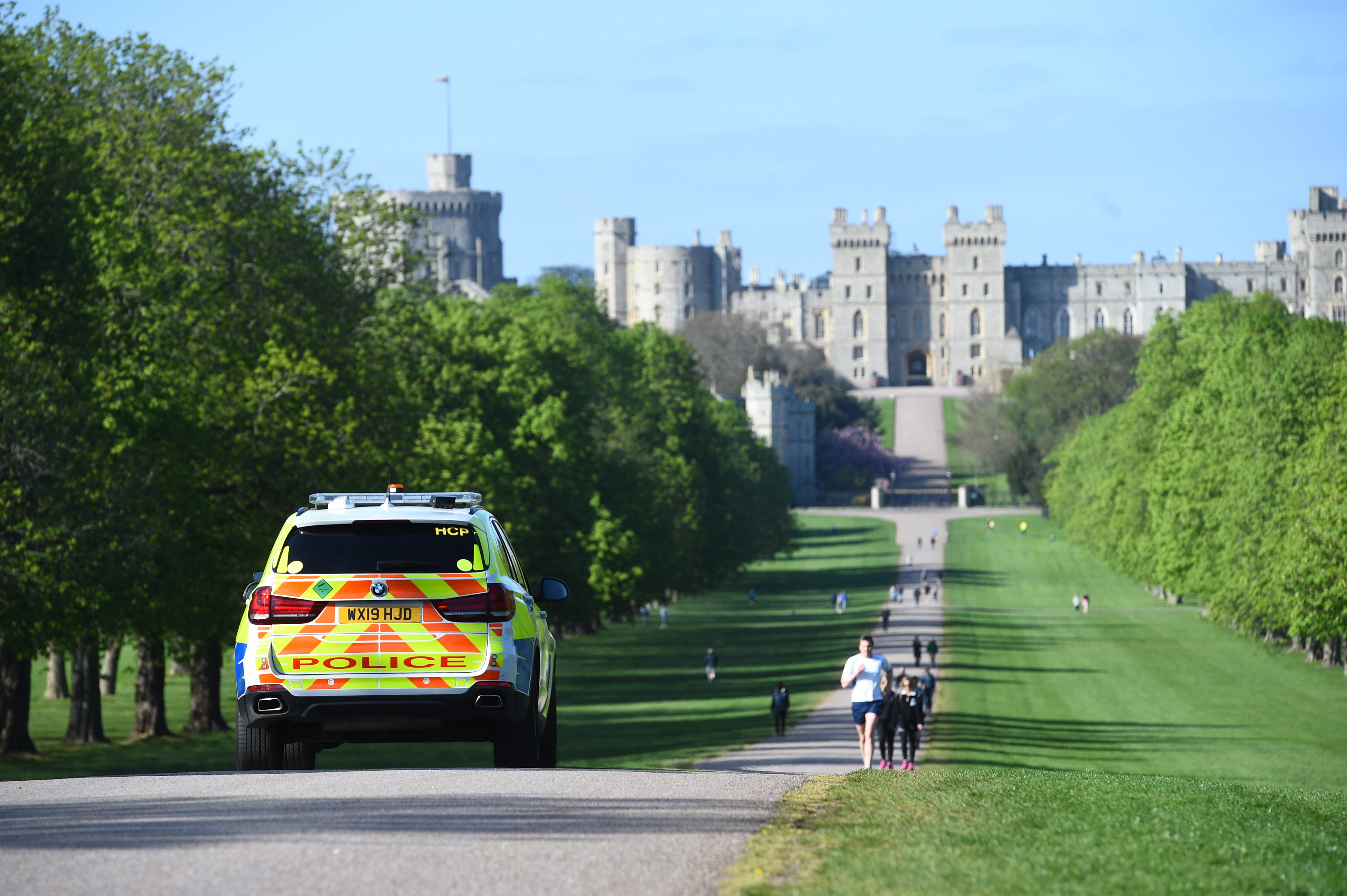 Police monitor people on the Long Walk in Windsor, as the UK continues in lockdown to help curb the spread of the coronavirus.