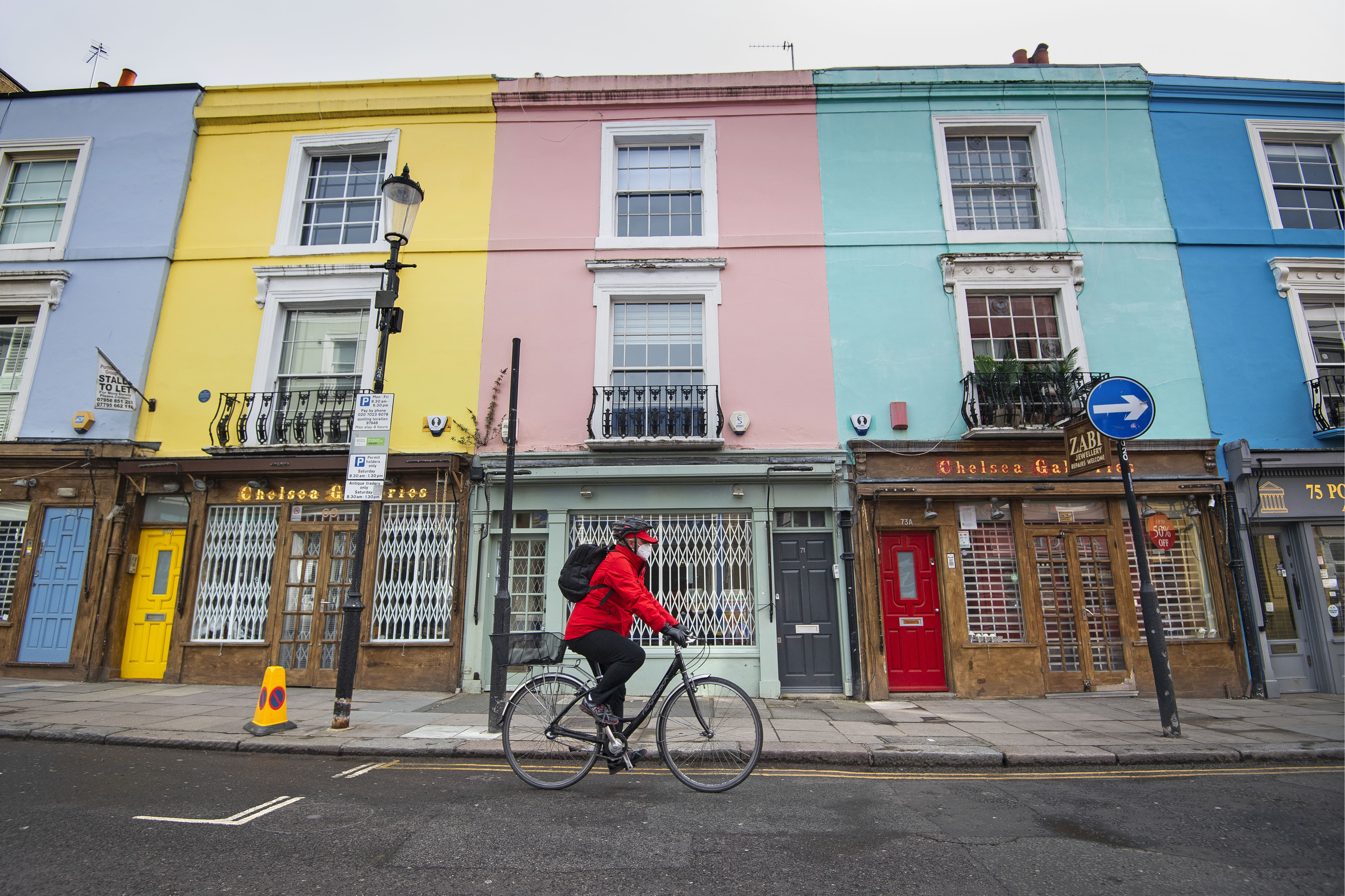 A cyclist wearing a face mask rides past closed up shops on Portobello Road in West London as the UK continues in lockdown to help curb the spread of the coronavirus.