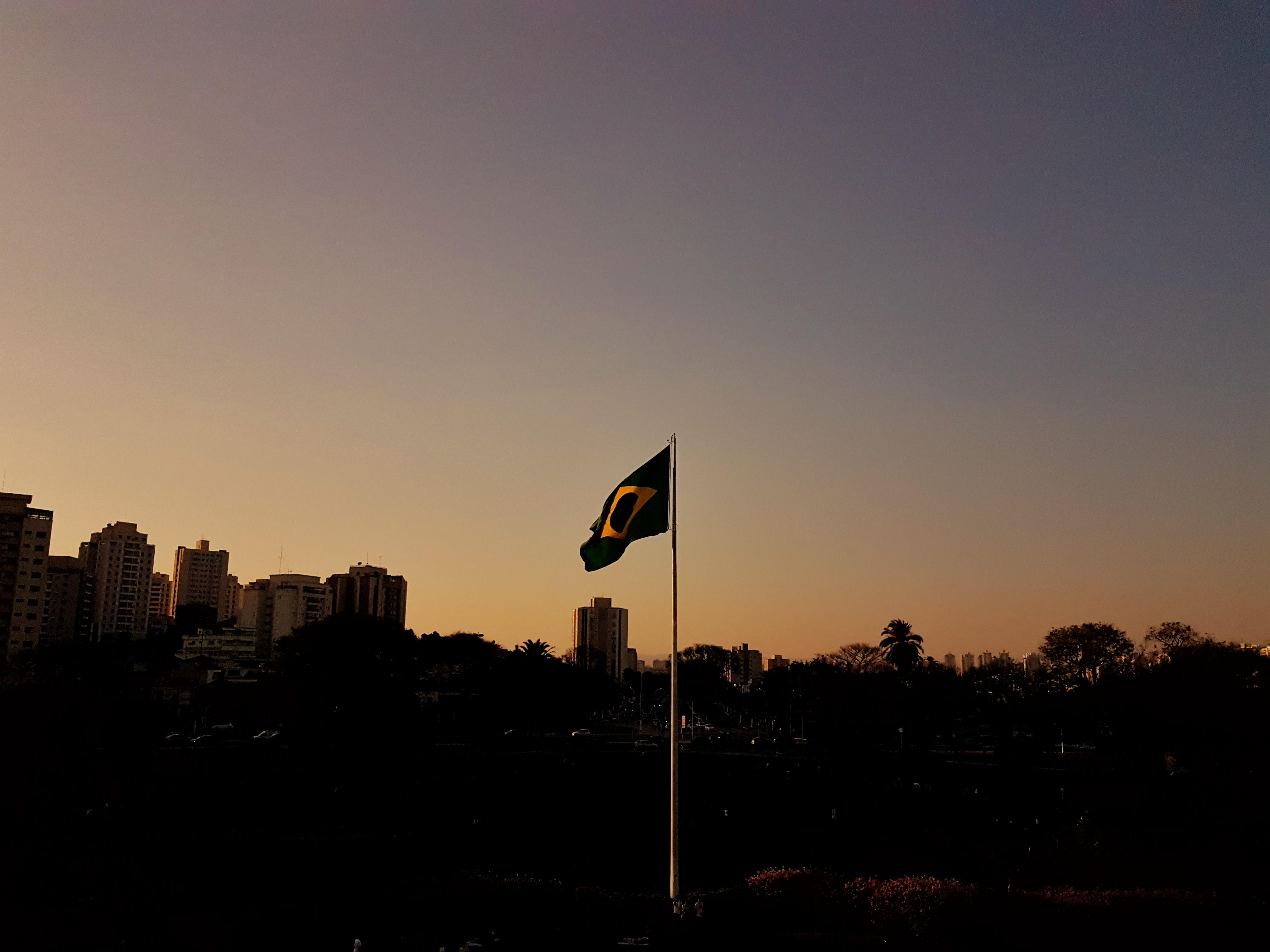 Bandeira do Brasil flamulando com penumbra do fim de tarde ao fundo.