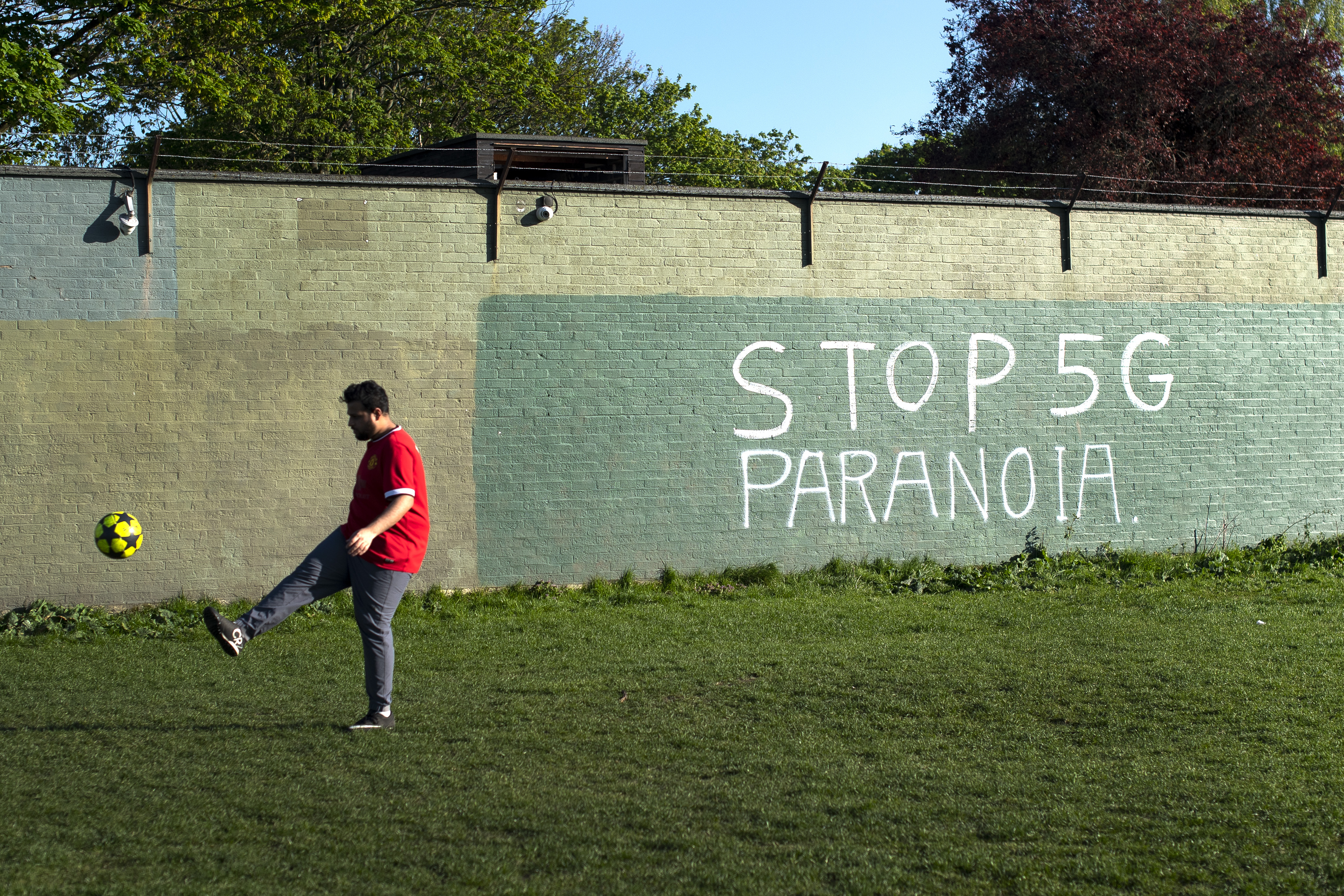 A man plays football in front of graffiti reading Stop 5G Paranoia on Wanstead Flats in East London as the UK continues in lockdown to help curb the spread of the coronavirus.