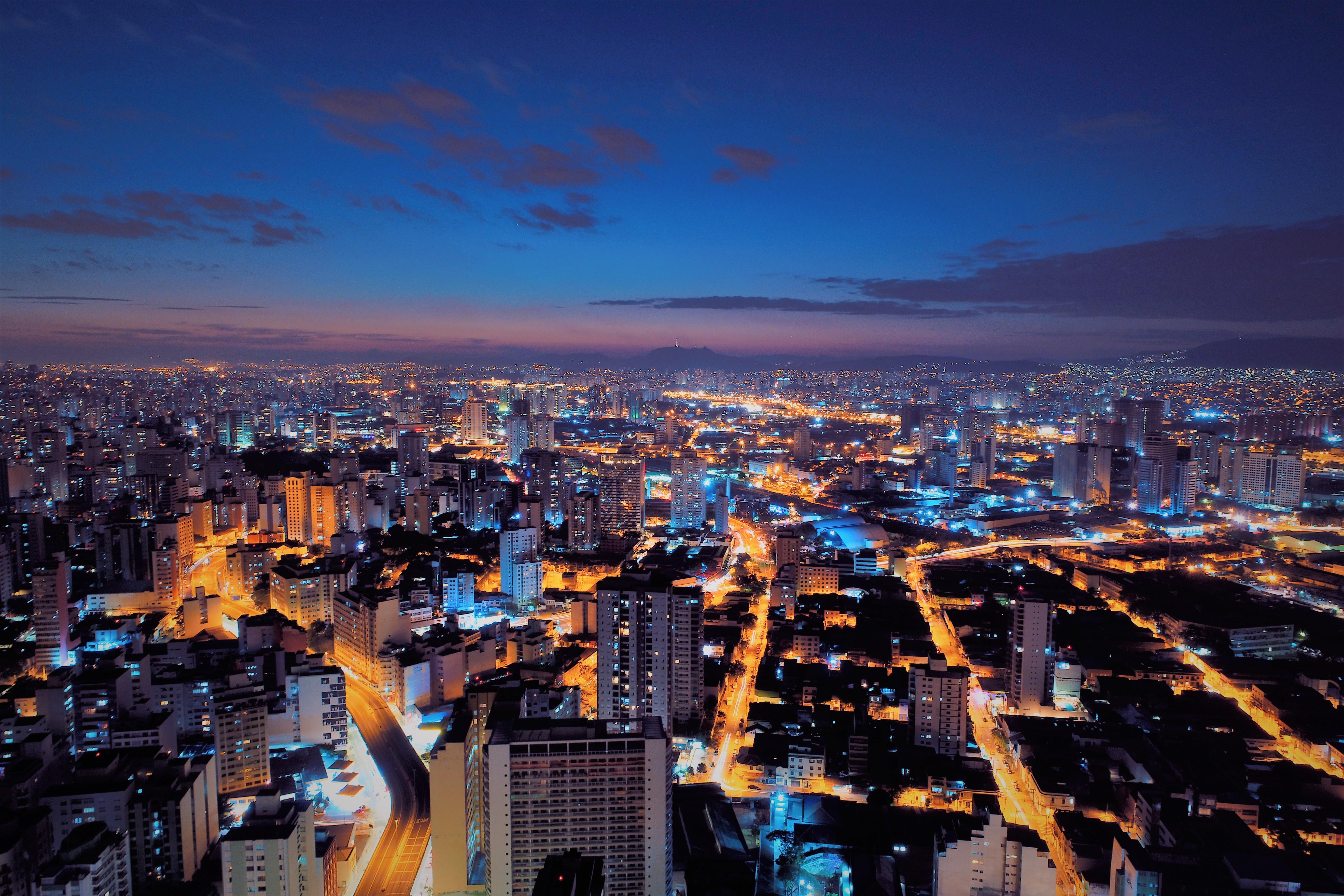 Cidade grande vista do alto durante um amanhecer com o horizonte ao fundo. As ruas estão iluminadas com luz laranja e o céu está com poucas nuvens.