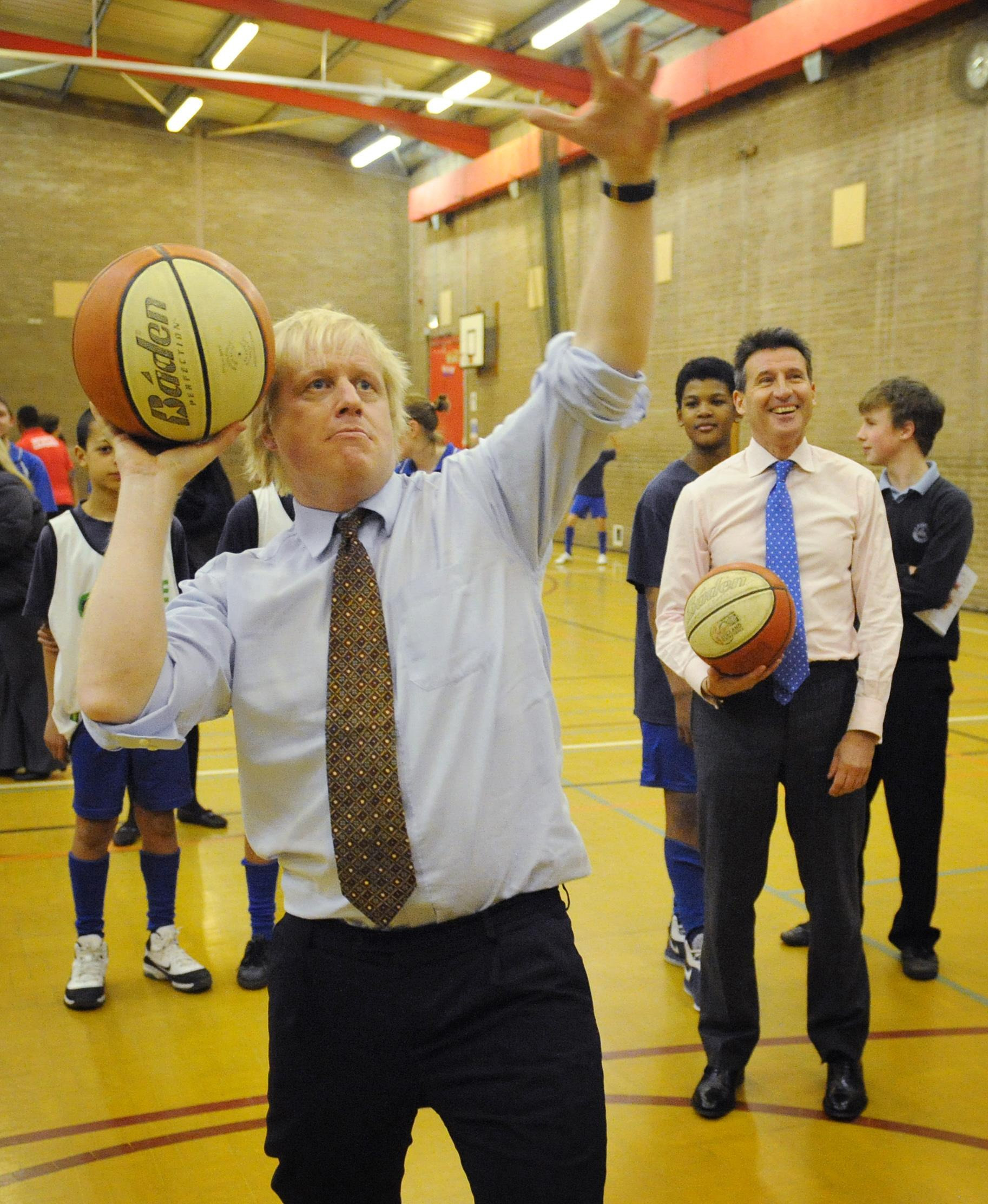 London 2012 Chairman Lord Coe (right) watches as London Mayor Boris Johnson plays basketball with pupils from Chiswick Community School in west London where they told the school how many Olympic tickets they would receive through the London 2012 Ticketshare scheme.