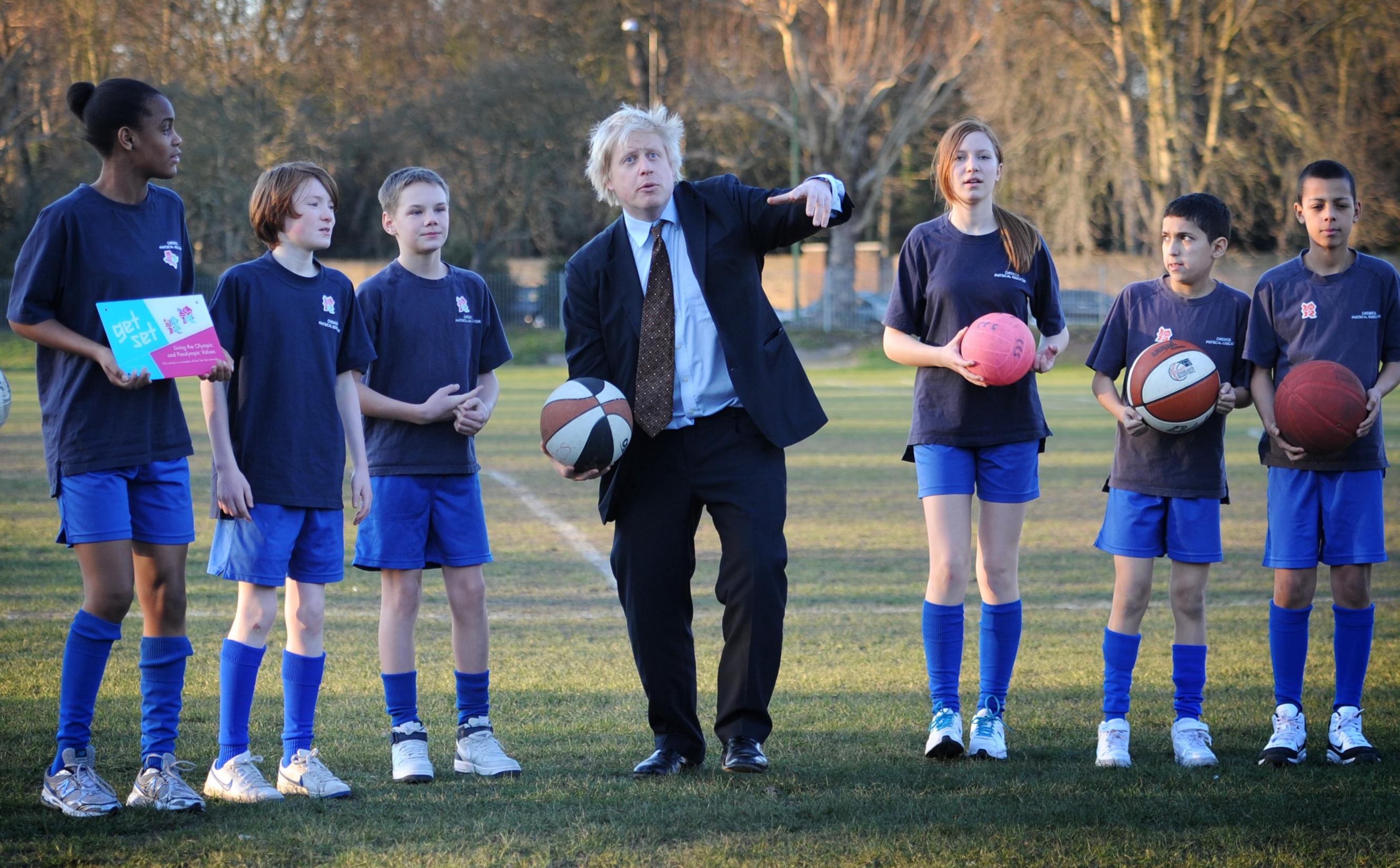 London Mayor Boris Johnson throws balls in the air with pupils from Chiswick Community School in west London where he and London 2012 Chairman Lord Coe told the school how many Olympic tickets they would receive through the London 2012 Ticketshare scheme.