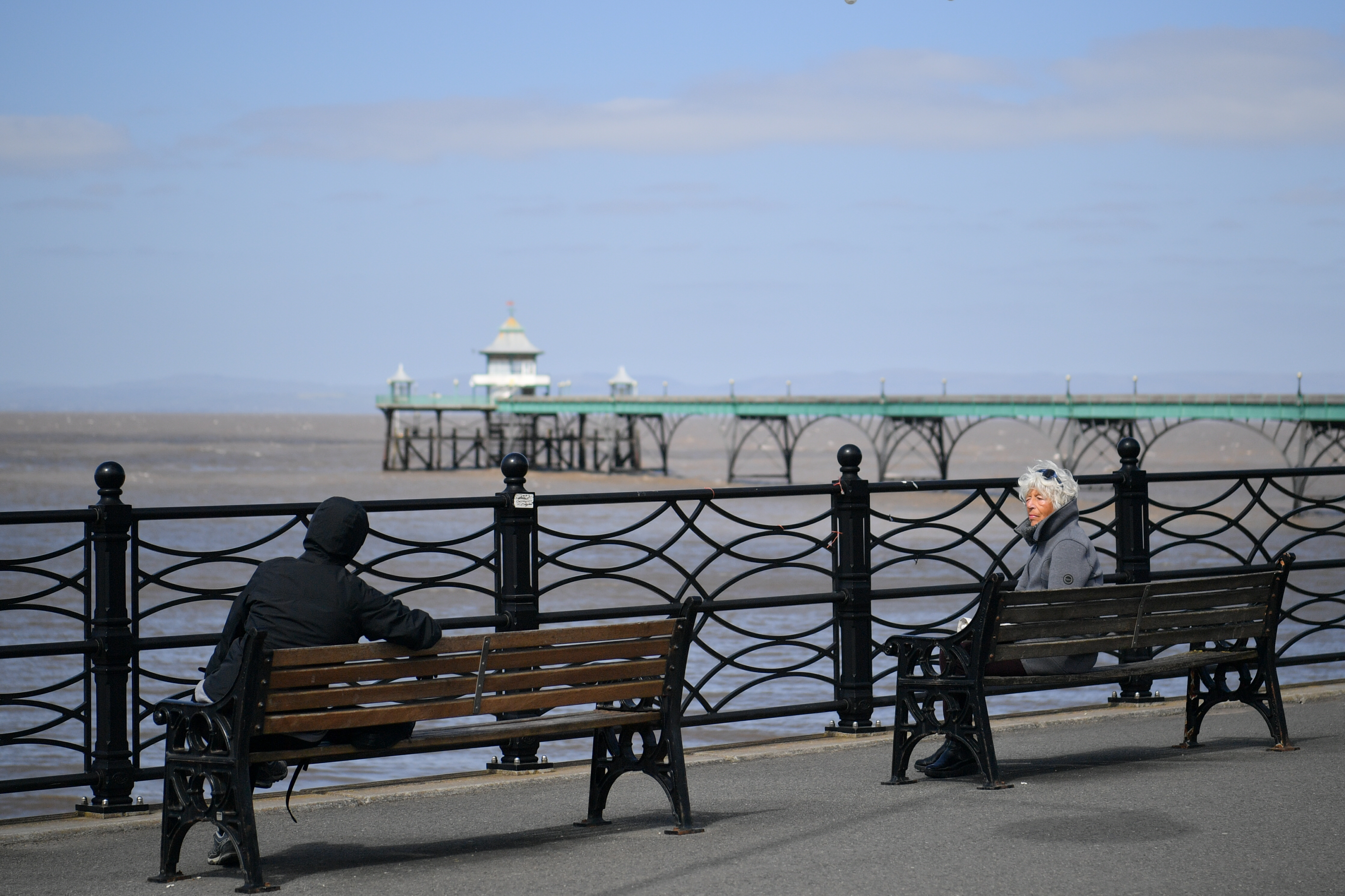 Two people practice social distancing while talking to each other sitting on benches in Clevedon on Easter Bank Holiday Monday at midday, as the UK continues in lockdown to help curb the spread of the coronavirus.
