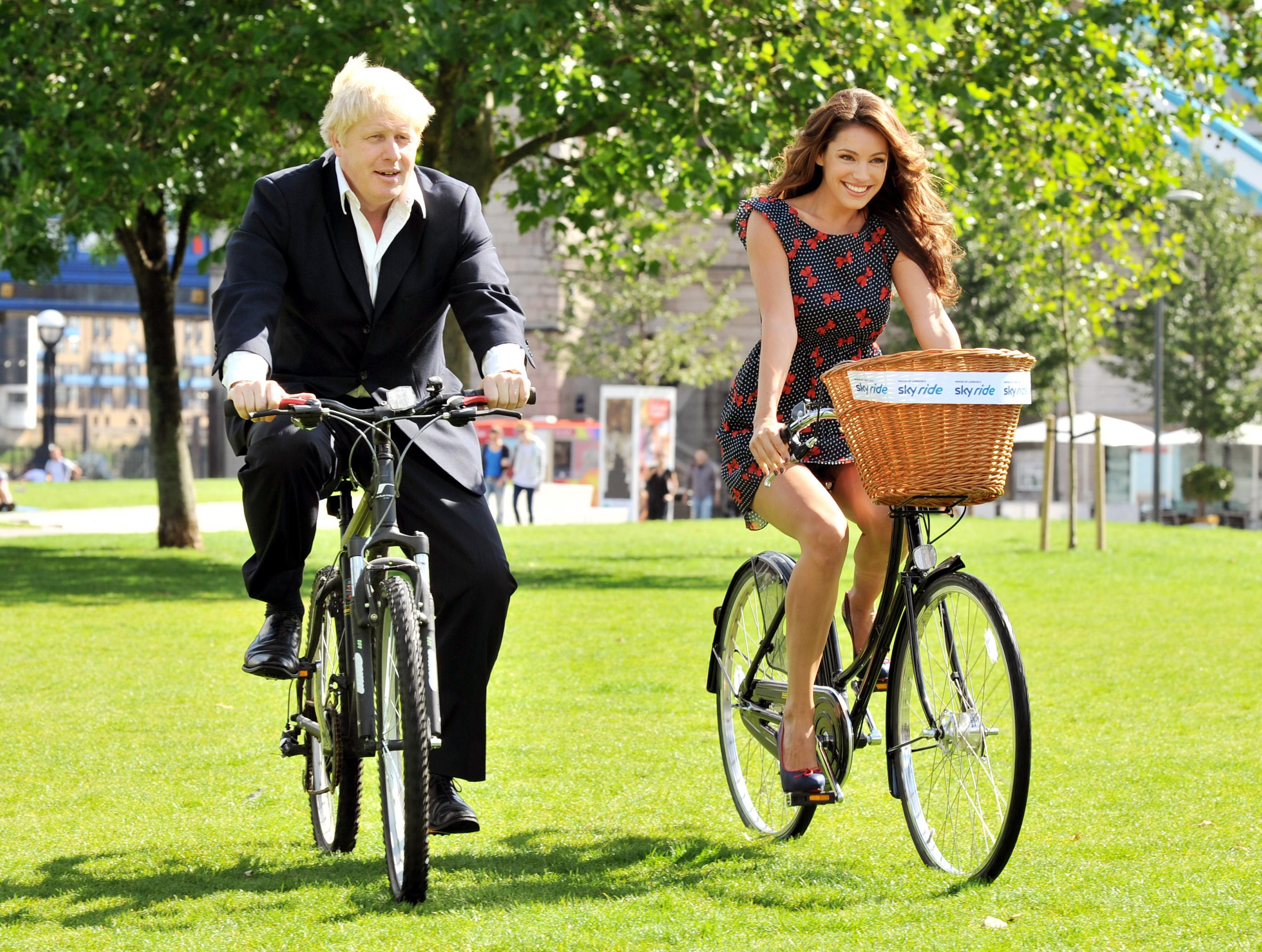 The Mayor of London Boris Johnson accompanied by Kelly Brook riding bicycles in central London to promote the London Skyride, this morning.