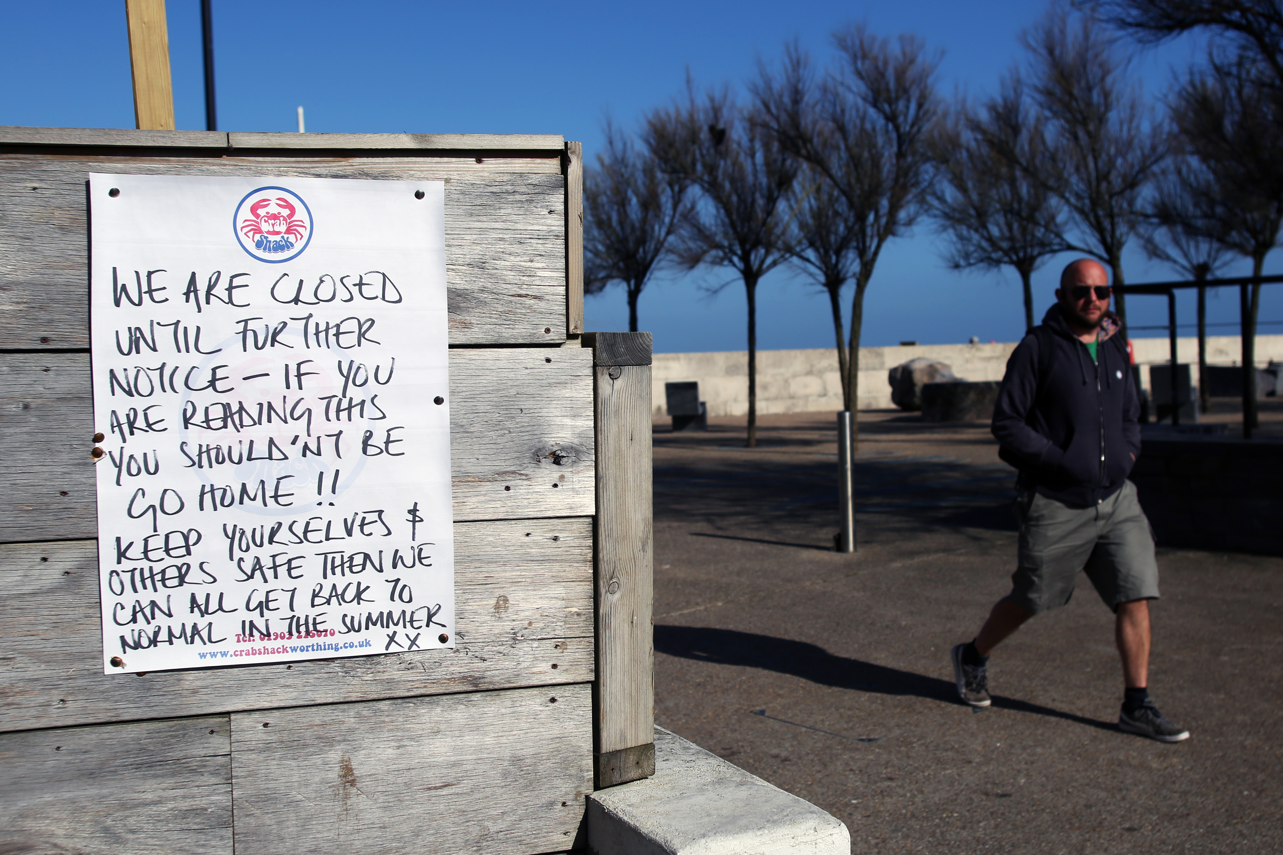 A man walks past a 'we are closed' sign at Crabshack in Worthing as the UK continues in lockdown to help curb the spread of the coronavirus.