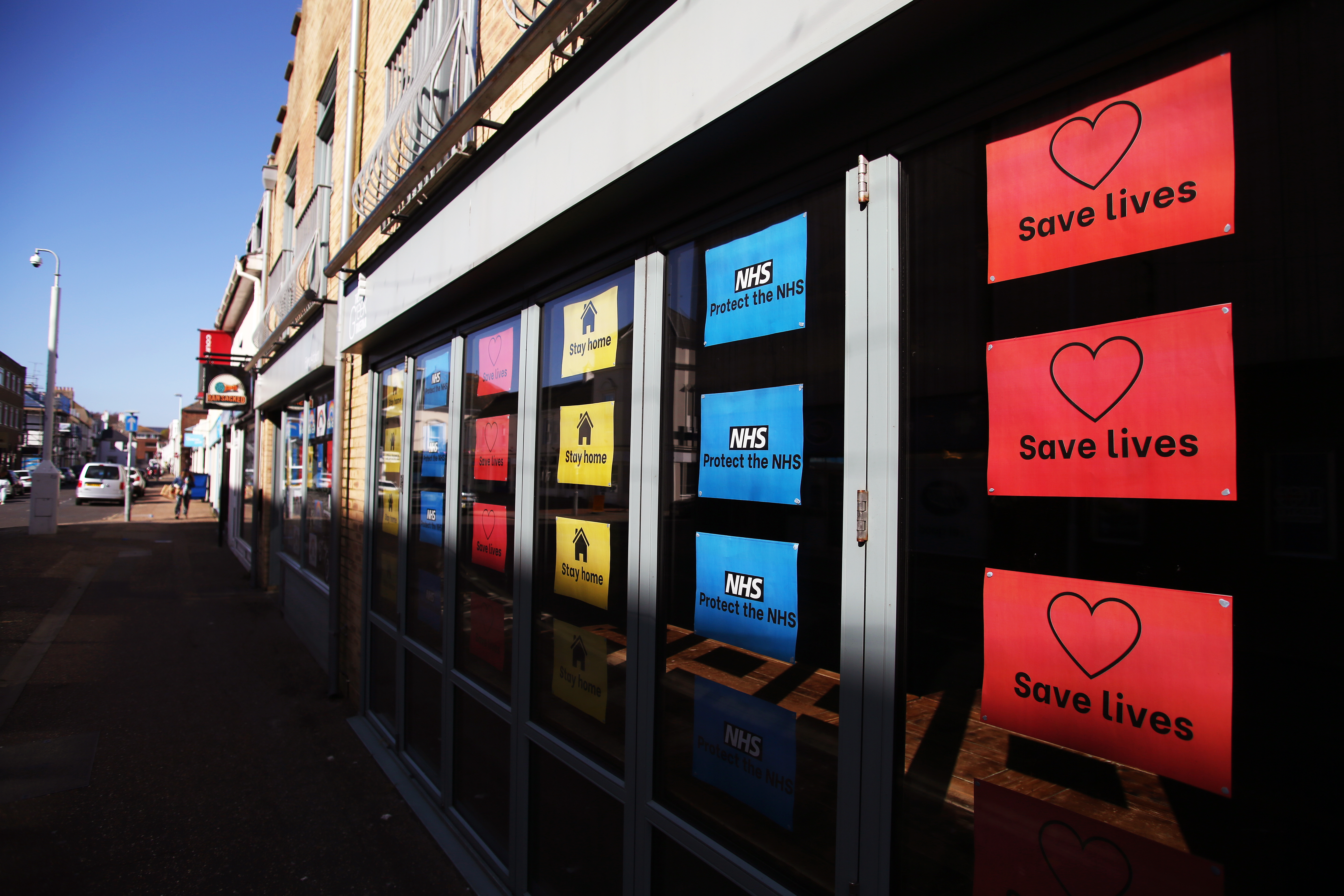Colourful signs in a shop window say 'stay home', 'protect the NHS' and 'save lives' as the UK continues in lockdown to help curb the spread of the coronavirus.