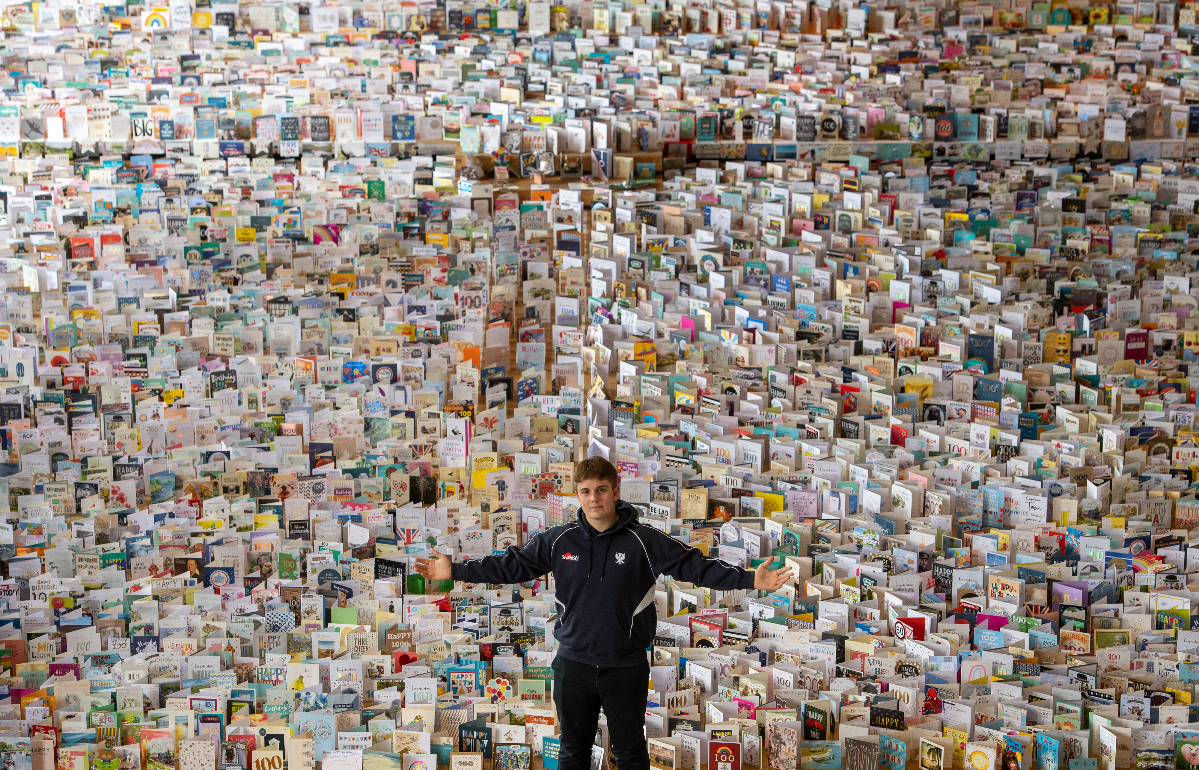 Captain Tom Moore's grandson Benjie, in the Great Hall of Bedford School, Bedfordshire, where over 120,000 birthday cards sent from around the world are being opened and displayed by staff. Captain Moore celebrates his 100th birthday on Thursday. (Photo by Joe Giddens/PA Images via Getty Images)