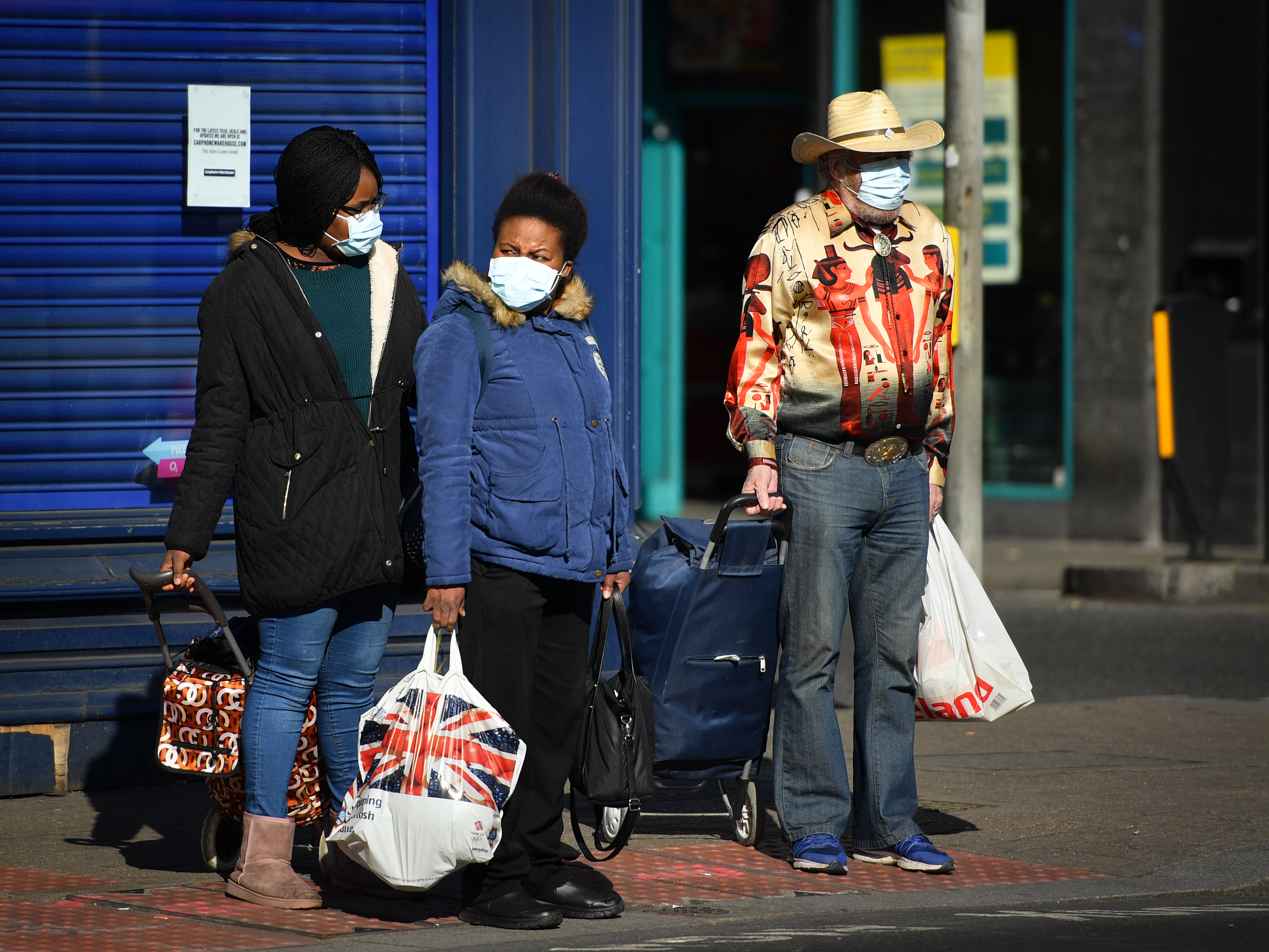 People wearing protective masks whilst shopping in South London as the UK continues in lockdown to help curb the spread of the coronavirus.