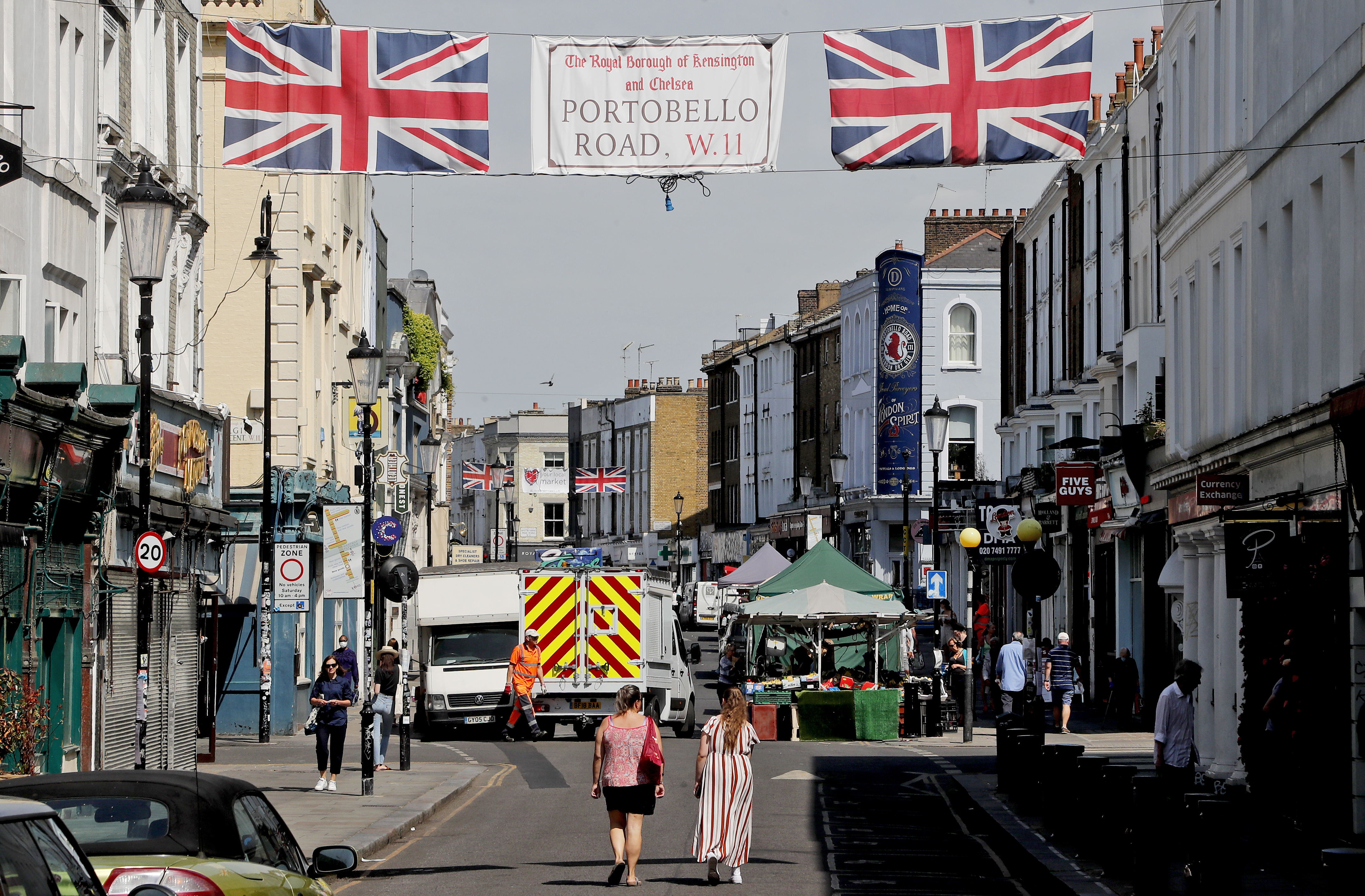 People walk along Portobello Road Market in London, Wednesday, May 27, 2020. Following the gradual easing of the COVID-19 lockdown, street markets will be allowed to reopen in Britain from Monday onwards. (AP Photo/Frank Augstein)