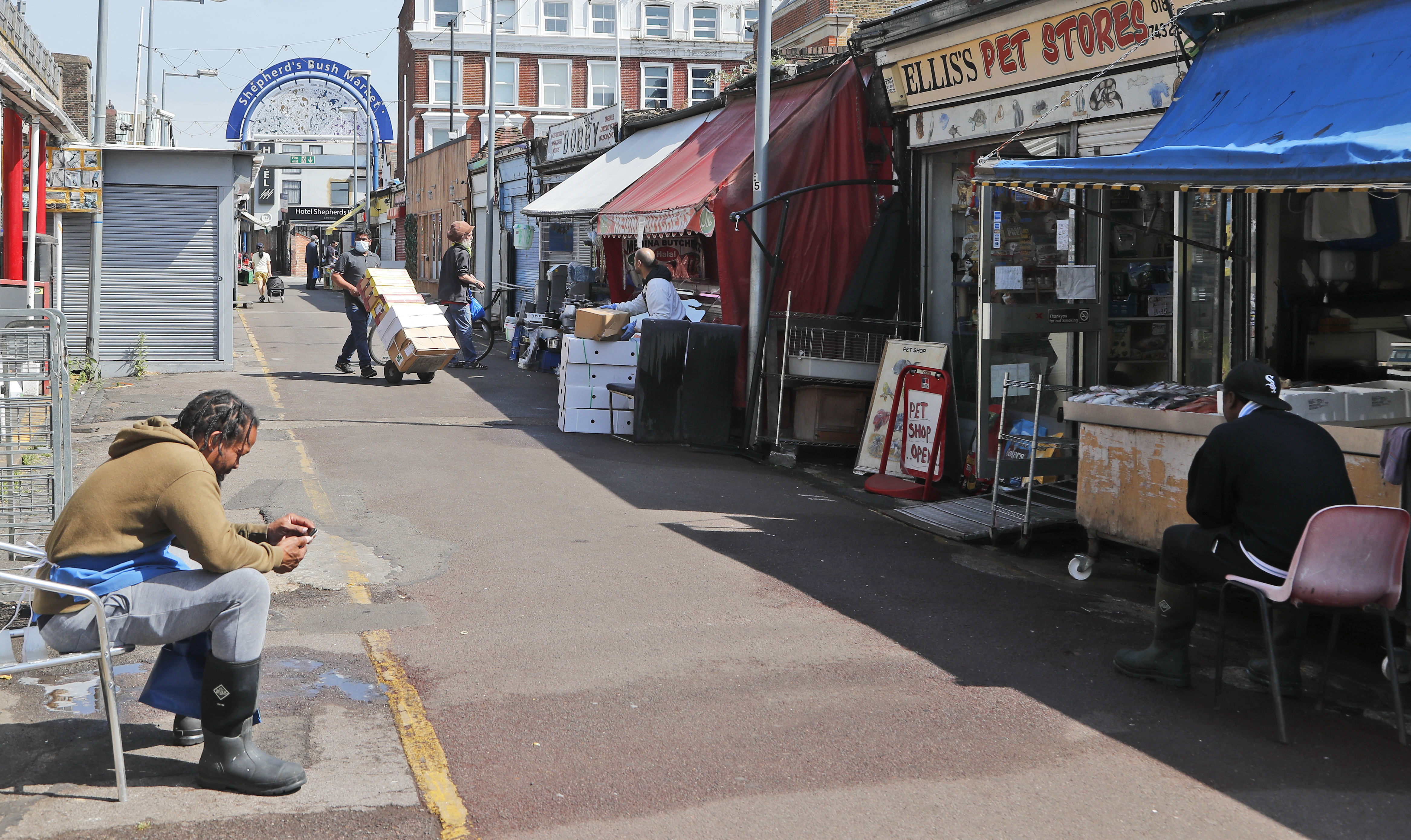 Shop owners wait for customers and prepare at Sherpherd's Bush Market in London, Wednesday, May 27, 2020. Following the gradual easing of the COVID-19 lockdown, street markets will be allowed to reopen in Britain from Monday onwards. (AP Photo/Frank Augstein)
