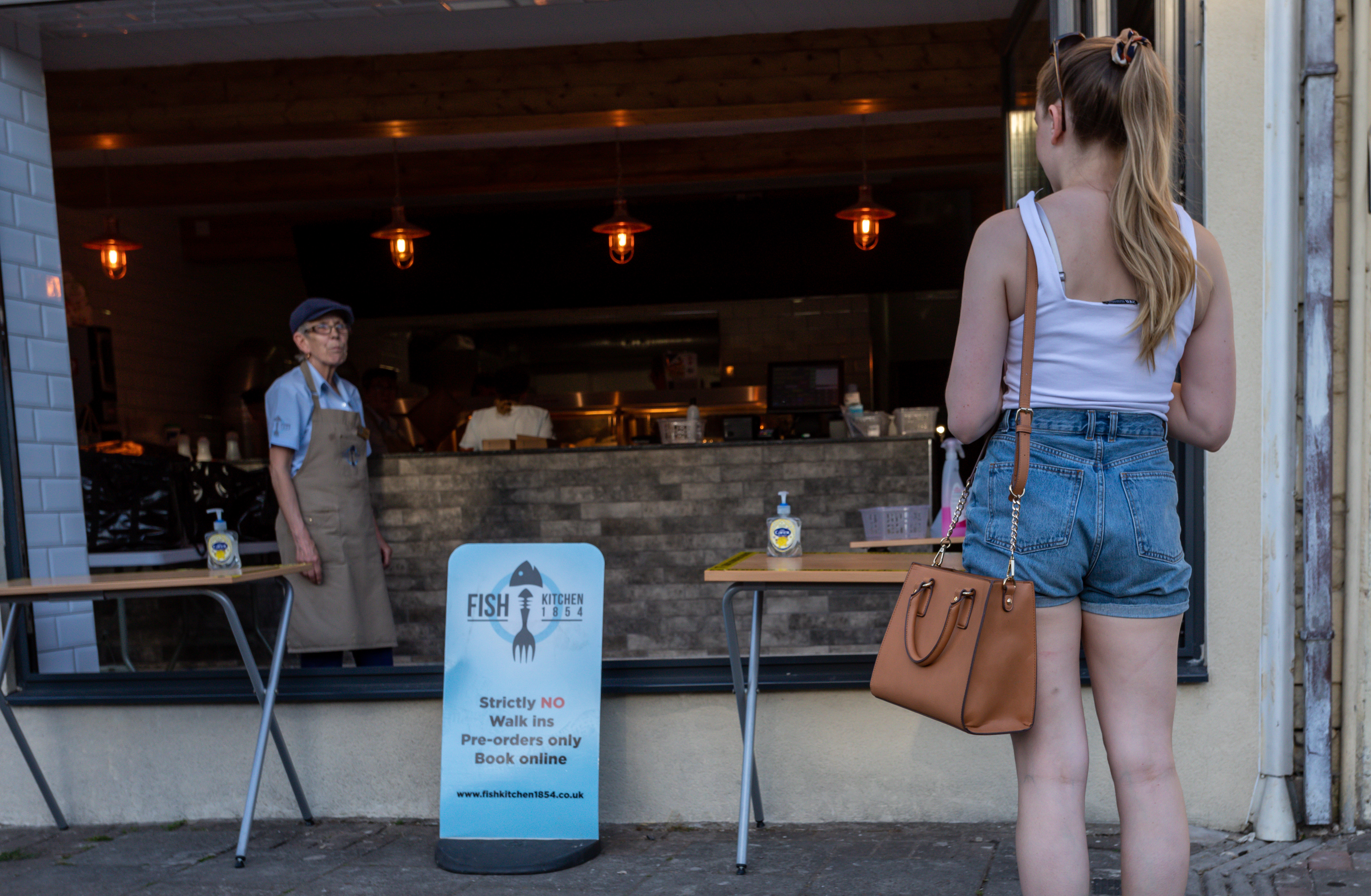 MAESYCWMMER, WALES  - MAY 29:  A customer waits to pick up her order from Fish Kitchen 1854, a traditional fish and chip shop which has reopened for online orders only on May 29, 2020 in Maesycwmmer, Wales, United Kingdom.The British government continues to ease the coronavirus lockdown by announcing schools will open to reception year pupils plus years one and six from June 1st. Open-air markets and car showrooms can also open from the same date.  (Photo by Huw Fairclough/Getty Images)