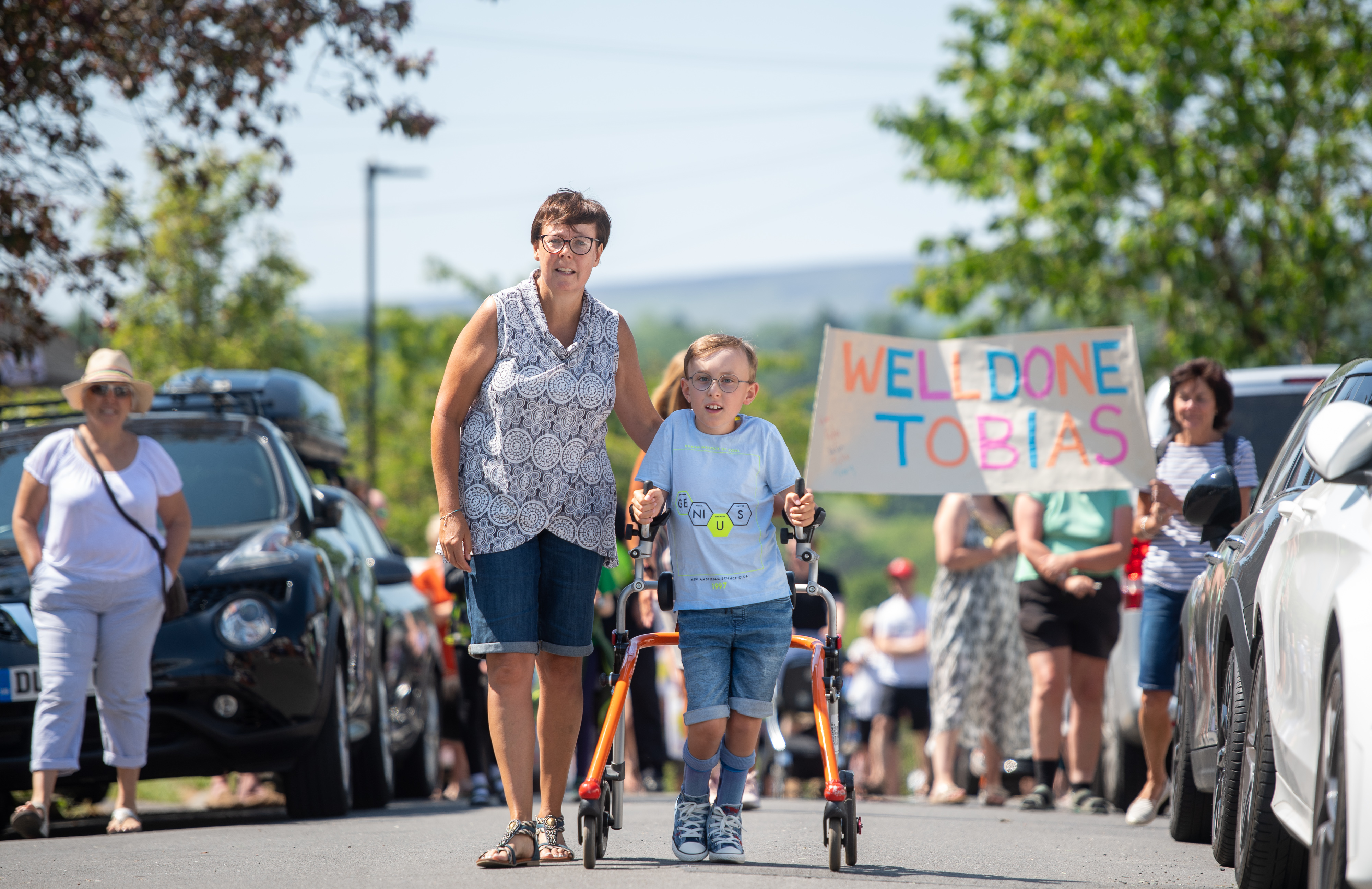 """Nine-year-old Tobias Weller, from Sheffield, who has cerebral palsy and autism, completes the final leg of a 26.2 mile total of a walk he has called his """"ginormous challenge"""", to walk a marathon using his walker during the lockdown."""