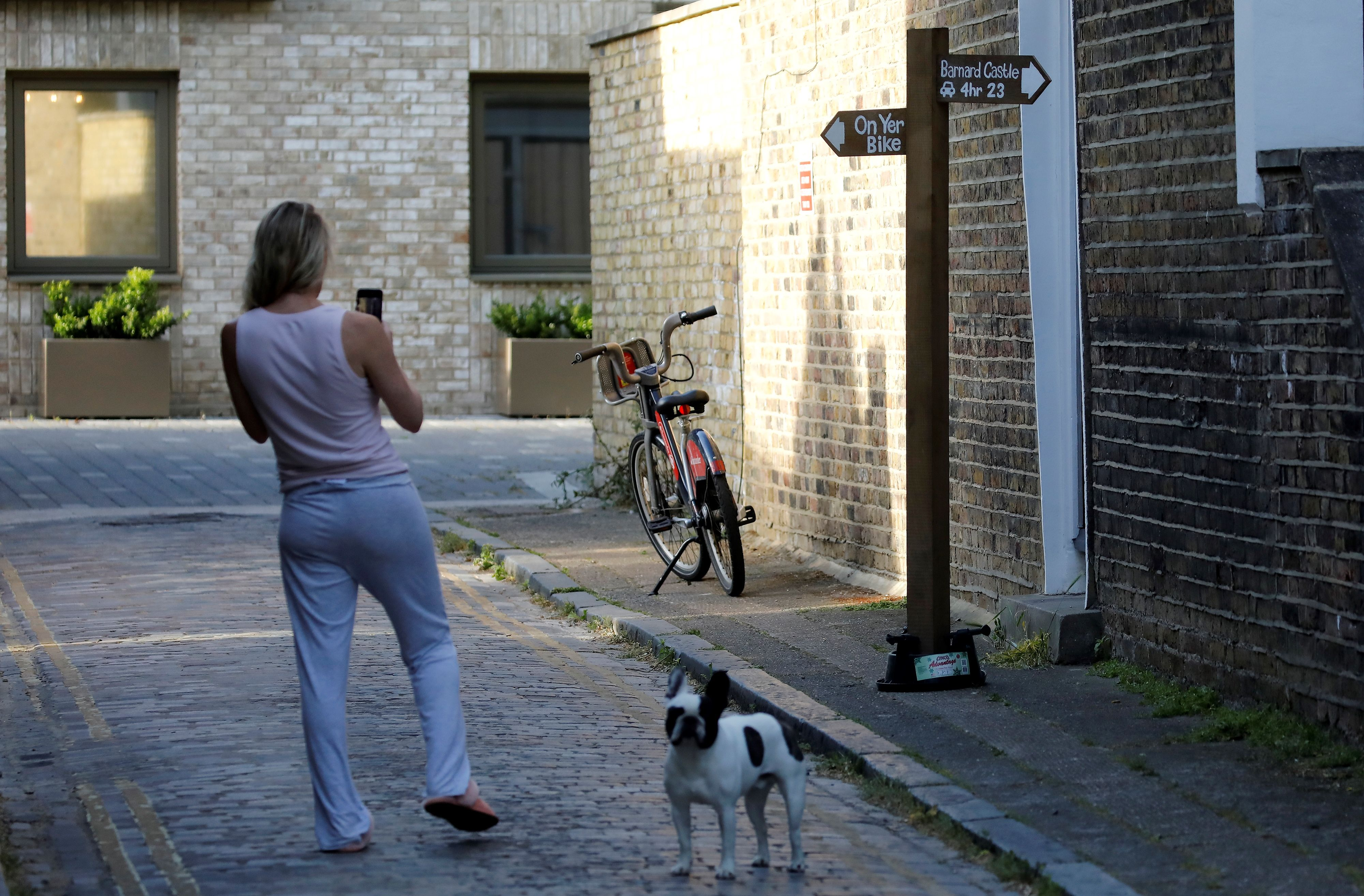 """A woman stands with a dog as she photographs a mock signpost, giving directions to Barnard Castle, southwest of Durham, placed near to the home of 10 Downing Street special advisor Dominic Cummings, in London on May 25, 2020 following his admission he drove and stayed in Durham during the coronavirus lockdown. - British Prime Minister Boris Johnson's top aide Dominic Cummings defied calls to resign on Monday over allegations that he broke coronavirus rules and undermined the government's response to the health crisis. Cummings told reporters that he acted """"reasonably and legally"""" when he drove across the country with his wife while she was suffering from the virus, despite official advice to stay at home. (Photo by Tolga AKMEN / AFP) (Photo by TOLGA AKMEN/AFP via Getty Images)"""