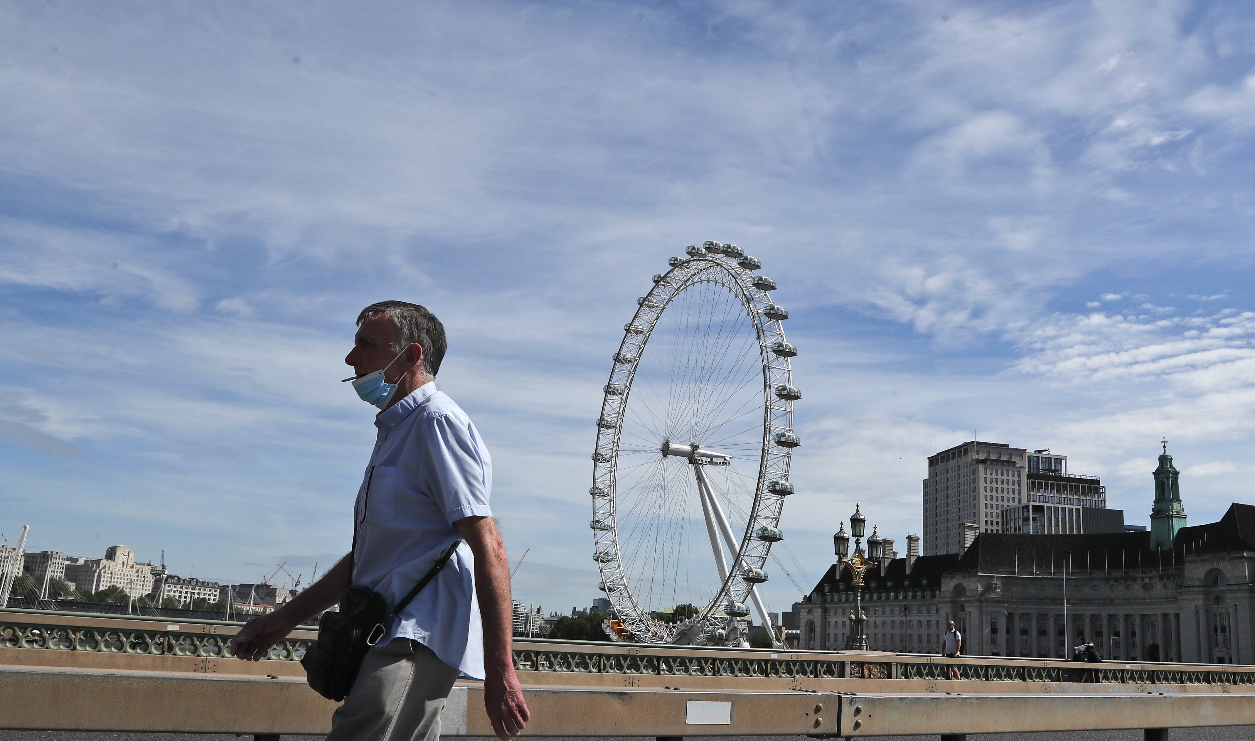 A man wearing a protective mask strolls across a bridge in central London, Tuesday, May 26, 2020, during hot weather following the gradual easing of the COVID-19 lockdown, allowing more outdoor recreation and letting some shops and businesses reopen. (AP Photo/Frank Augstein)