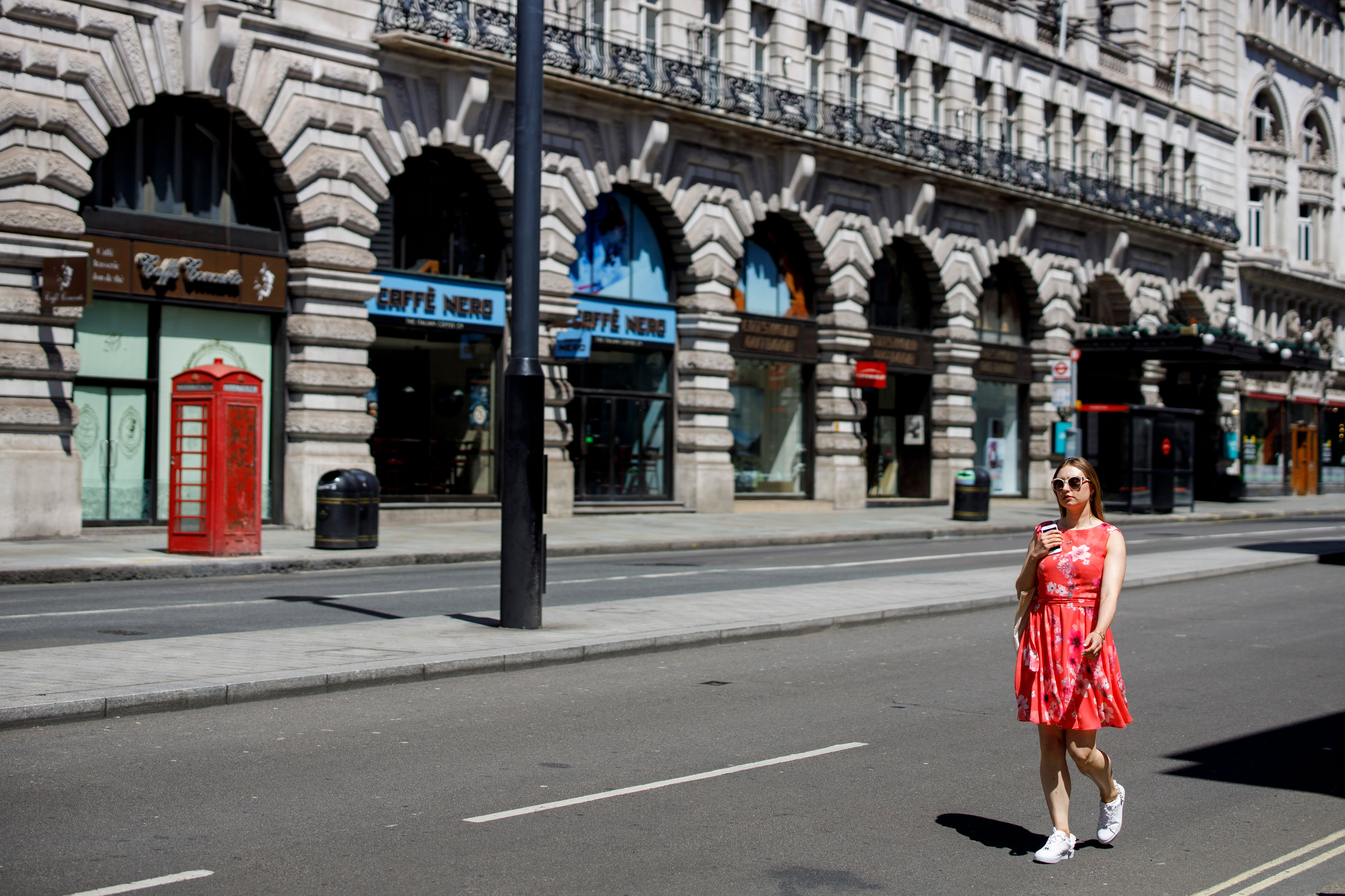 A woman walks past closed shops and restaurants on Piccadilly in central London's main high street retail shopping area on May 29, 2020 ahead of some shops reopening from their coronavirus shutdown from next week. - The UK Prime Minister announced on May 28 that some English schools and shops would reopen from next week people would a little more freedom to meet others in public as he tried to plot Britain's path through a health disaster that has officially claimed 37,837 lives -- second only to the United States -- and devastated the economy. (Photo by Tolga AKMEN / AFP) (Photo by TOLGA AKMEN/AFP via Getty Images)