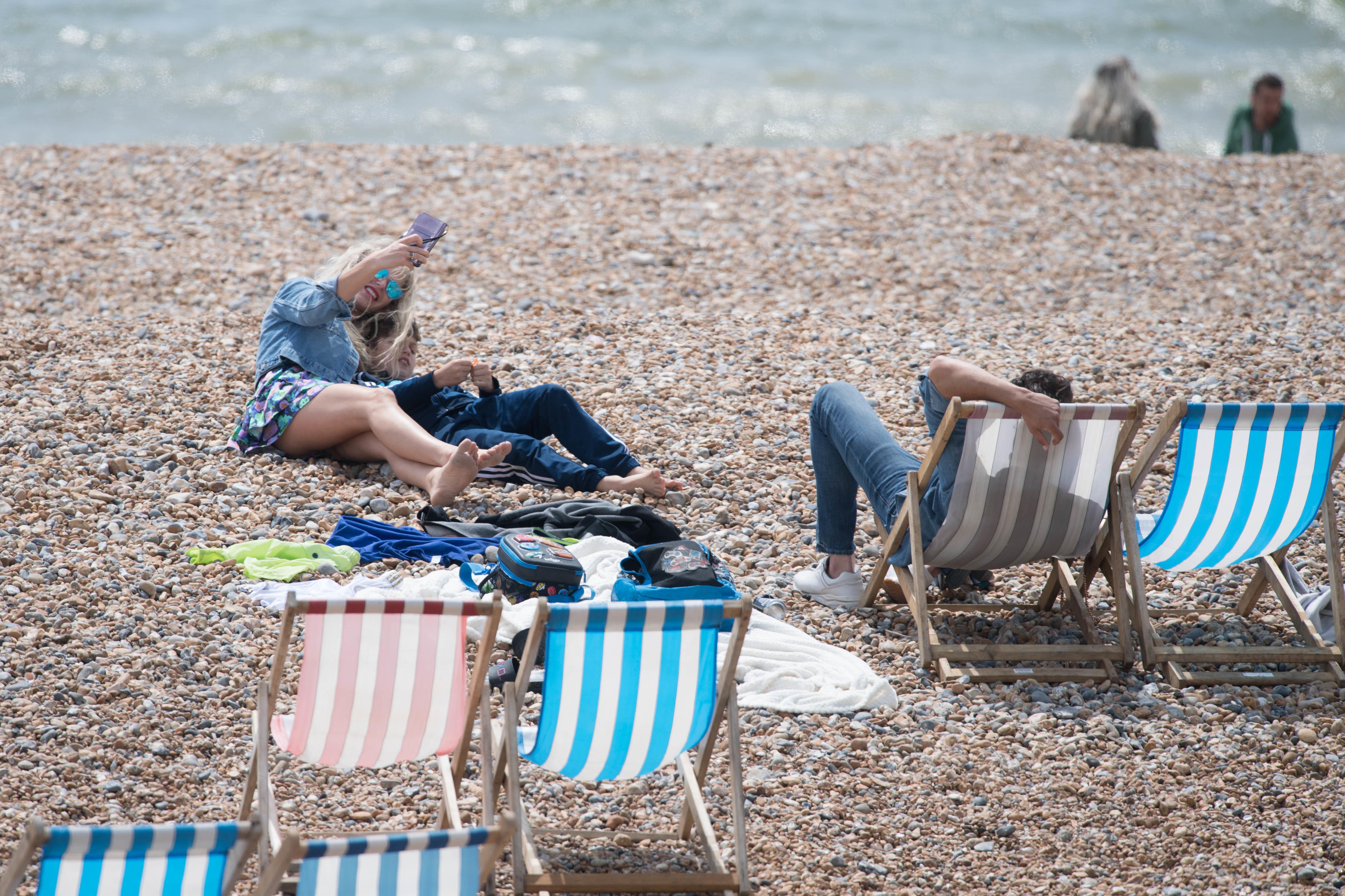 Visitors to Brighton beach in East Sussex take a selfie photograph today as the UK continues in lockdown to help curb the spread of the coronavirus. PA Photo. Picture date: Sunday May 17, 2020. See PA story HEALTH Coronavirus. Photo credit should read: Stefan Rousseau/PA Wire