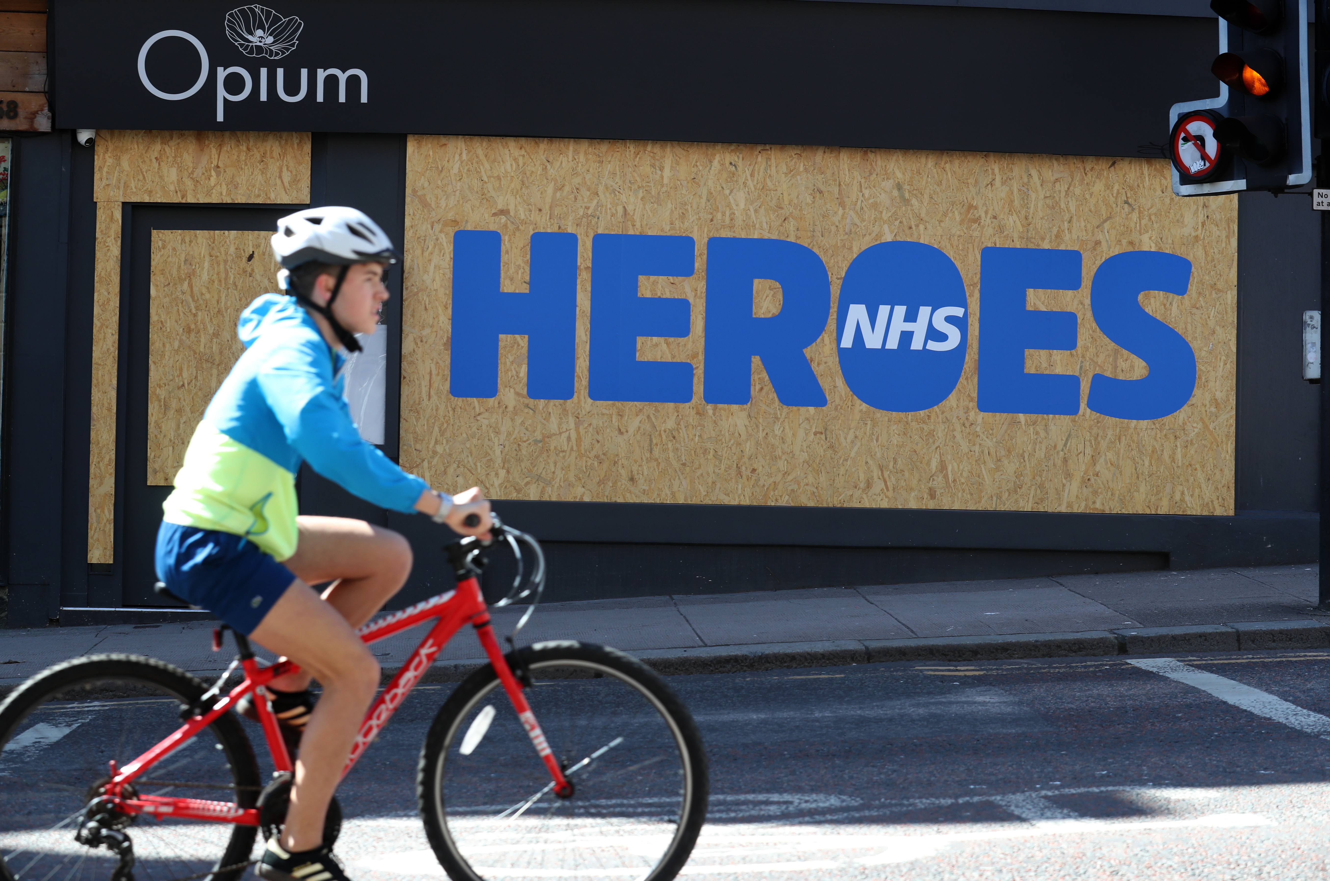 A cyclist passes a boarded up shop in Glasgow with the wording HEROES written on it as a tribute to the NHS as the UK continues in lockdown to help curb the spread of the coronavirus.