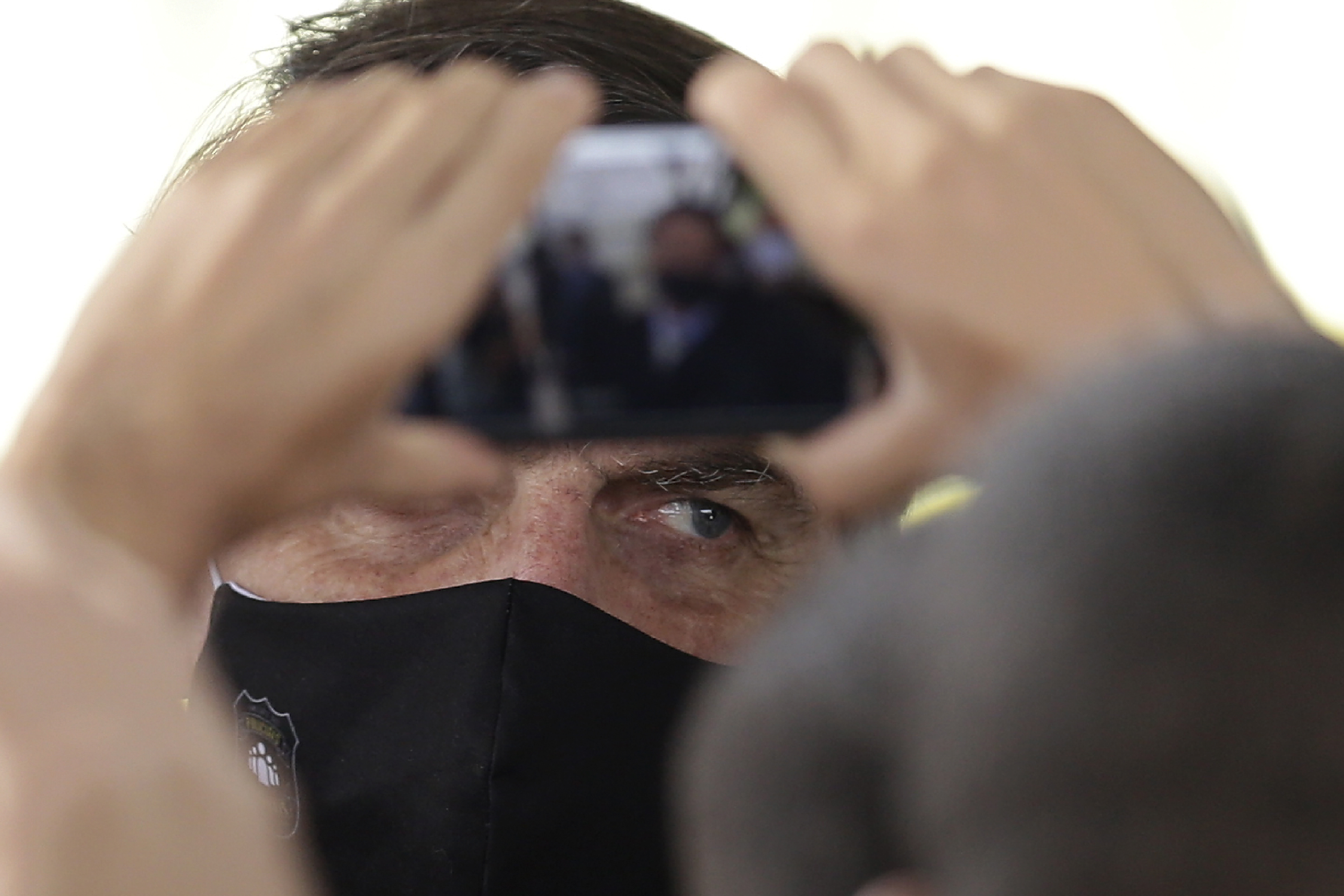 Brazil's President Jair Bolsonaro, wearing a face mask amid the new coronavirus pandemic, faces supporters taking pictures with cell phones as he leaves his official residence of Alvorada palace in Brasilia, Brazil, Monday, May 25, 2020. (AP Photo/Eraldo Peres)