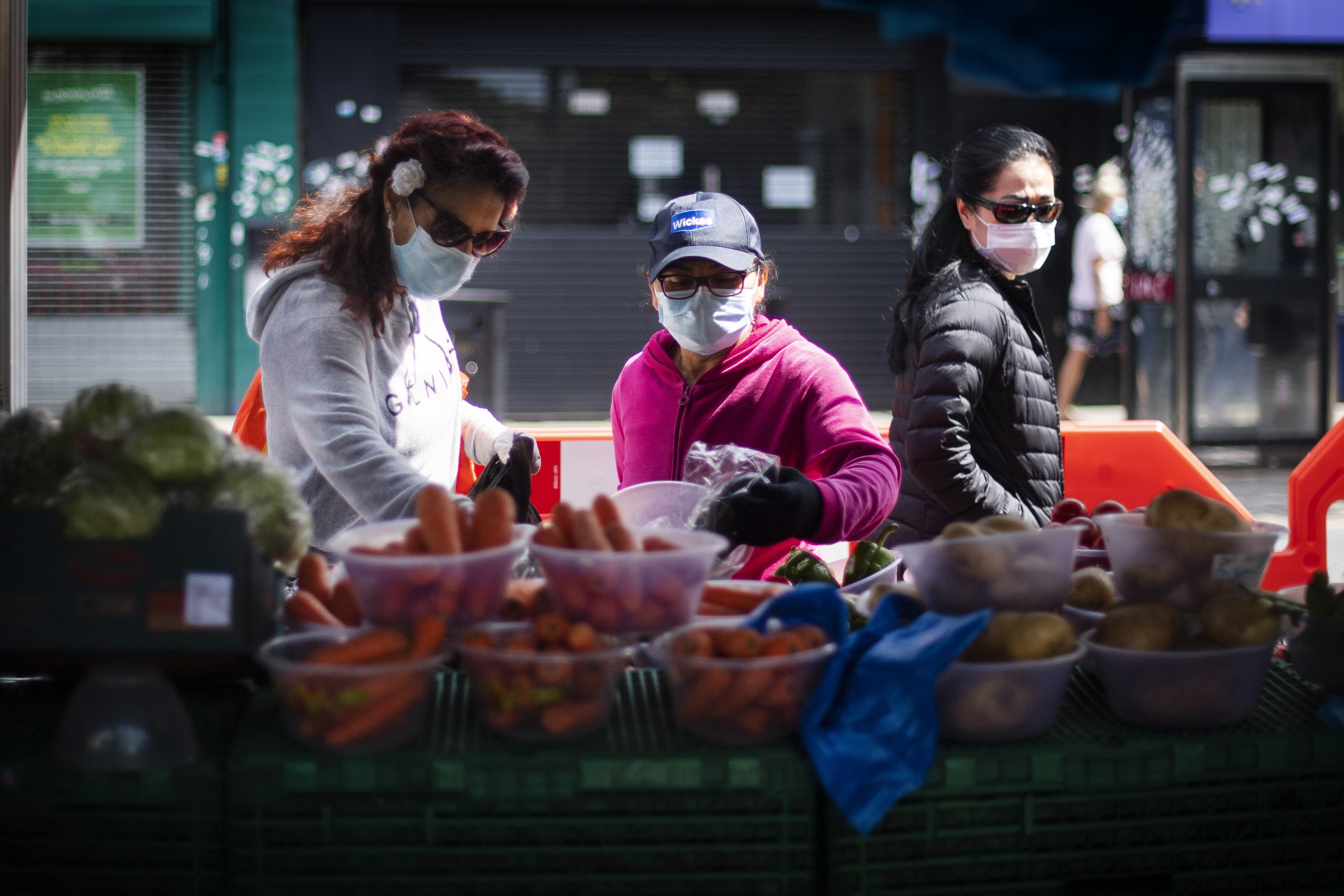 Three women wearing protective face masks buy fruit and vegetables at a high street market stall in East Ham, east London, as the UK continues in lockdown to help curb the spread of the coronavirus.