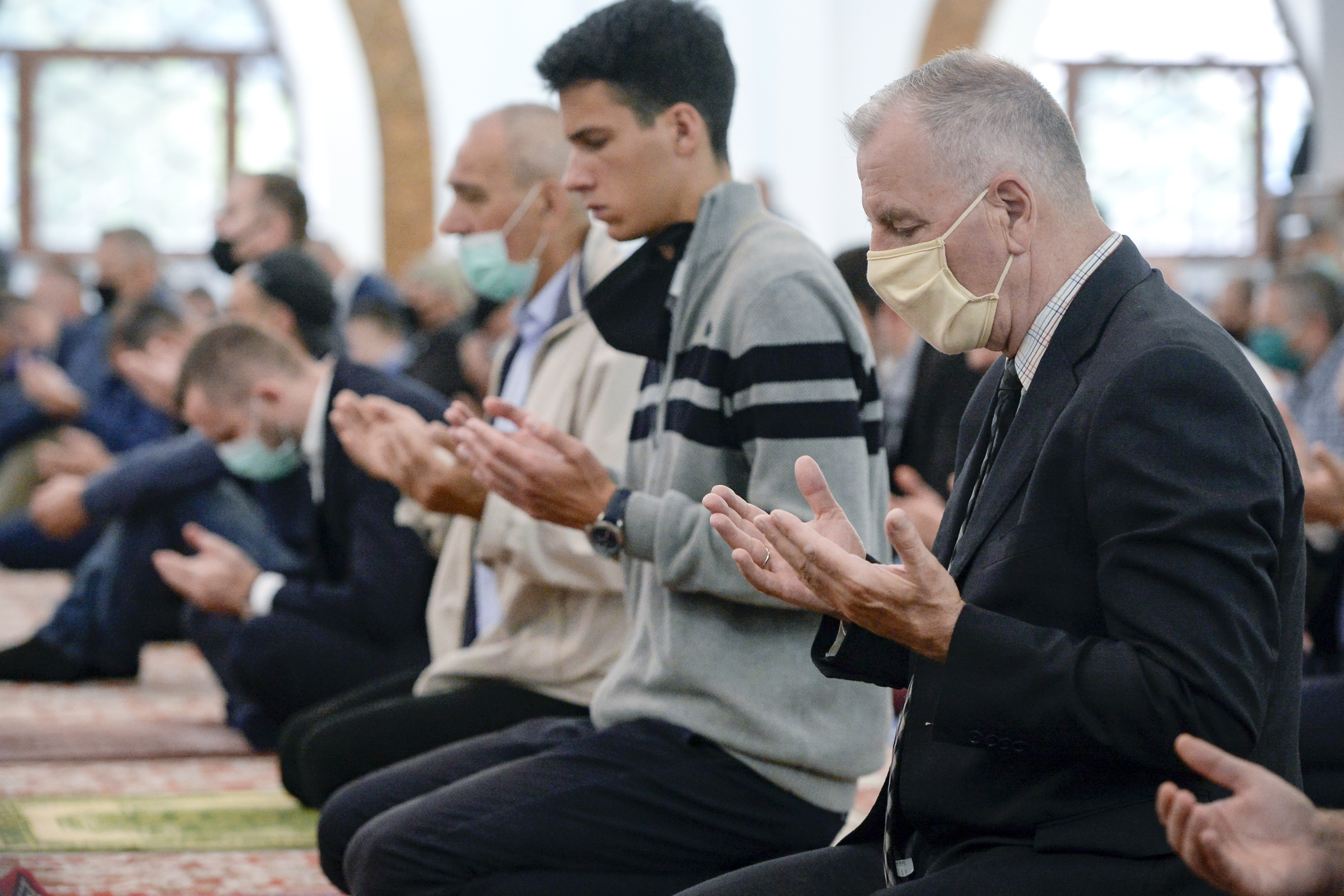 Bosnian muslims, some wearing face masks to protect themselves from the COVID-19 infection, attend Eid al-Fitr prayers in Sarajevo, Bosnia, Sunday, May 24, 2020. Muslims worldwide are marking a muted religious festival of Eid al-Fitr, the end of the fasting month of Ramadan _ a usually joyous three-day celebration that has been significantly toned down due to the new coronavirus outbreak.(AP Photo/Kemal Softic)