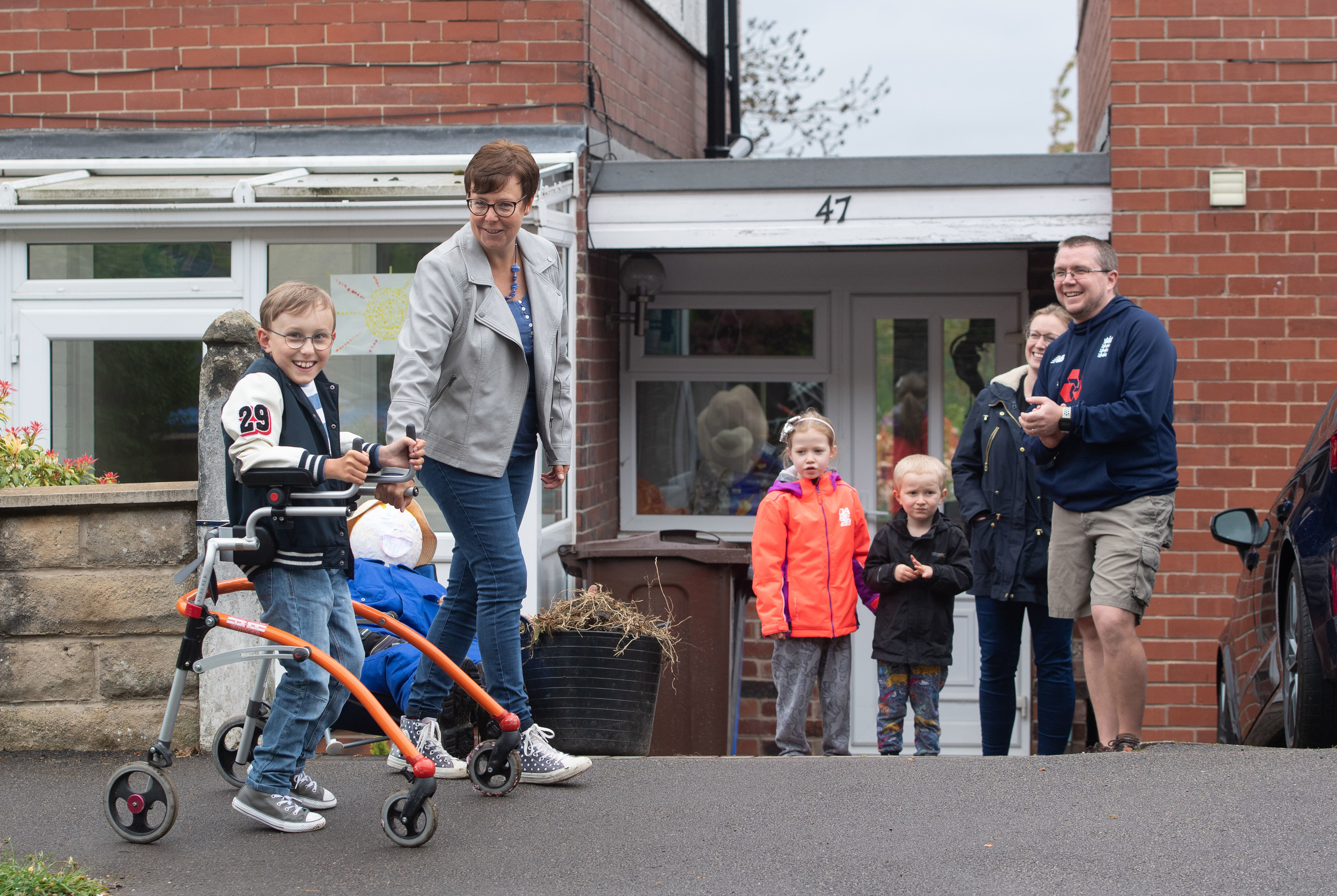 """File photo dated 29/04/20 of Tobias Weller, who has cerebral palsy and autism, being cheered on by neighbours as he walks along the street outside his home in Sheffield, South Yorkshire. Nine-year-old Tobias, who cannot stand or walk unaided, is gearing up for the final leg of what he has called his """"ginormous challenge"""" to walk a marathon using his walker during the lockdown."""