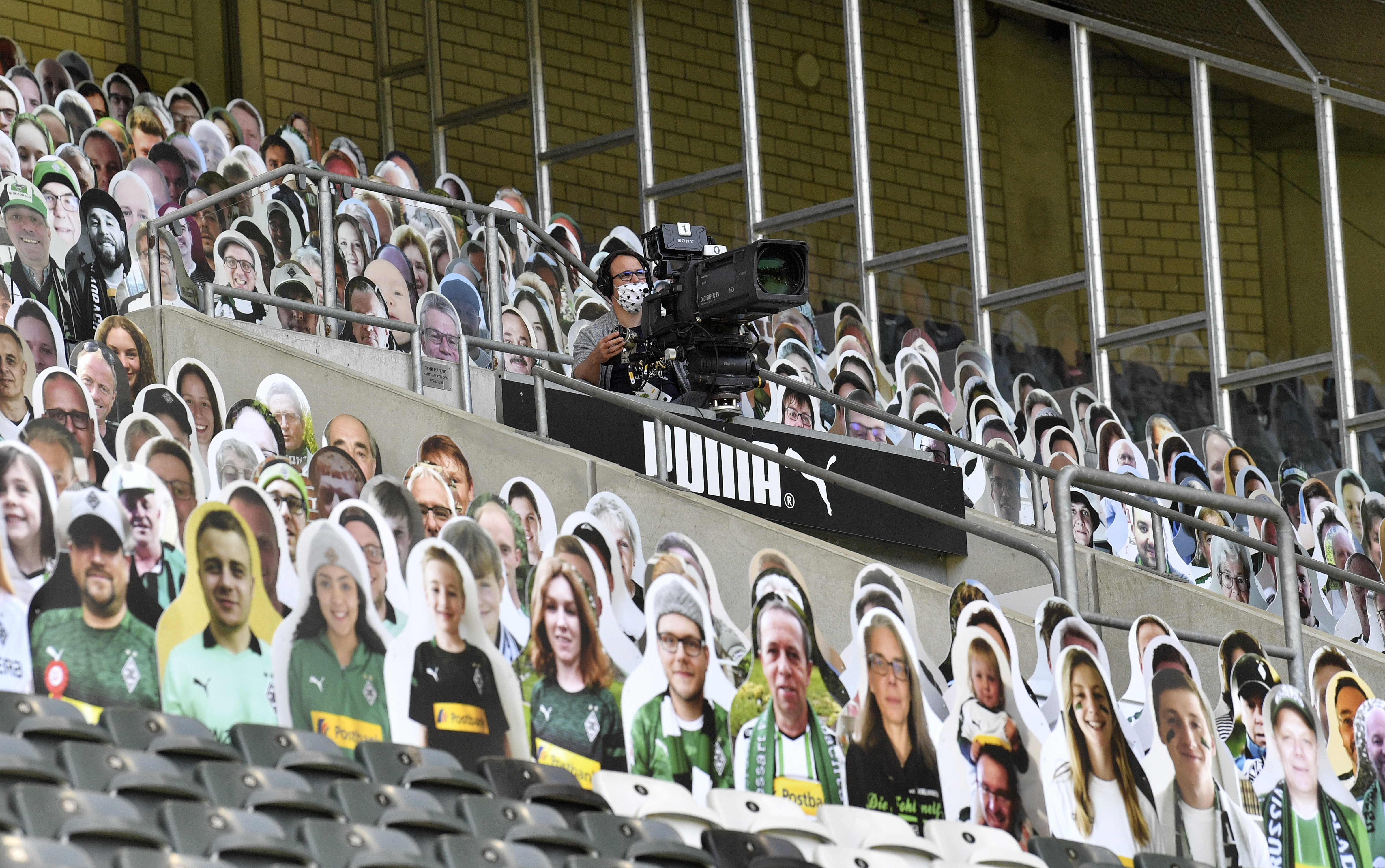 A TV cameraman wears a face mask seen between cardboards with photos of Moenchengladbach fans displayed on the stands prior the German Bundesliga soccer match between Borussia Moenchengladbach and Union Berlin in Moenchengladbach, Germany, Sunday, May 31, 2020. The German Bundesliga becomes the world's first major soccer league to resume after a two-month suspension because of the coronavirus pandemic. (AP Photo/Martin Meissner, Pool)
