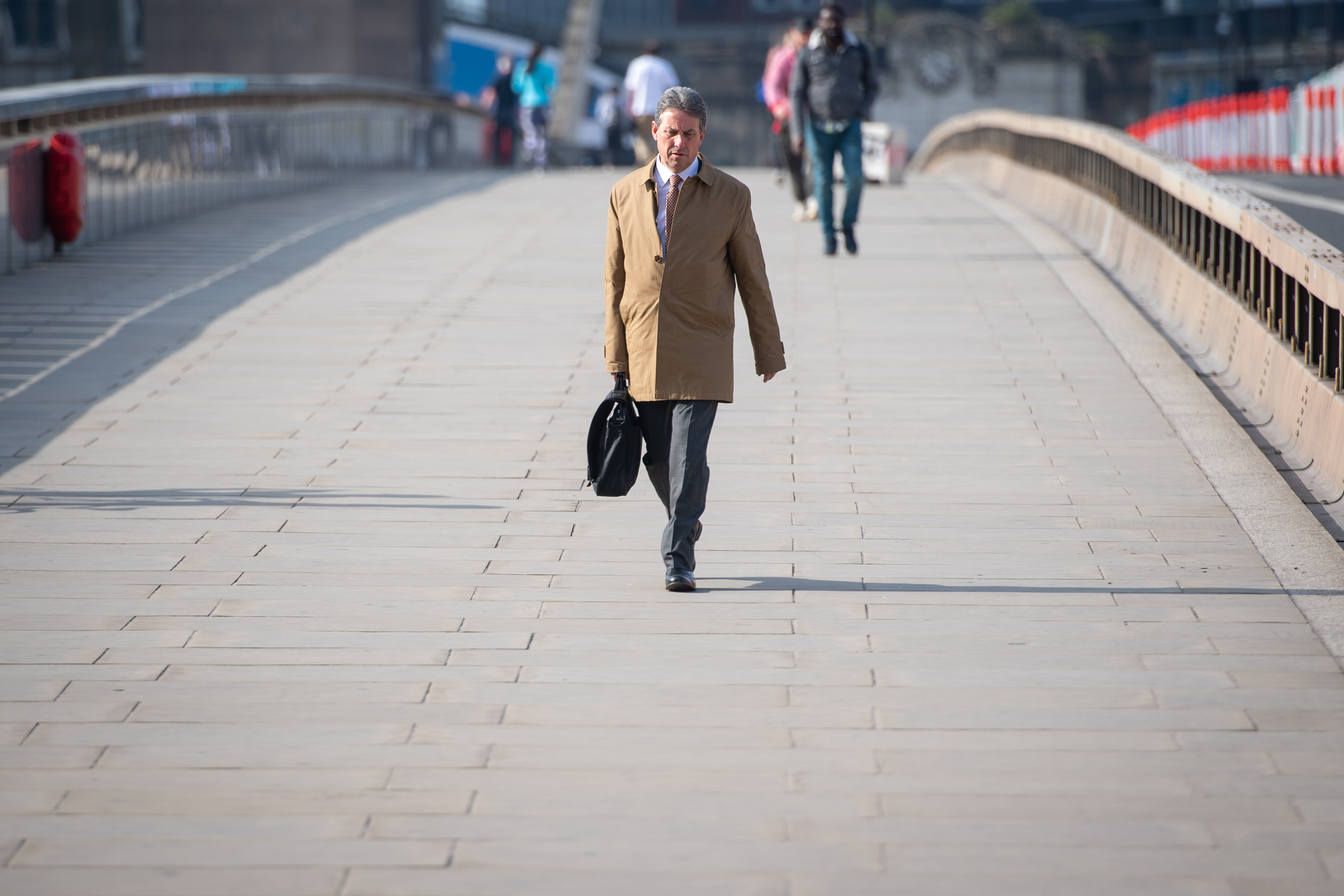 A man walks over London Bridge towards the City financial district during what would normally be morning rush hour, as the UK continues in lockdown to help curb the spread of the coronavirus.