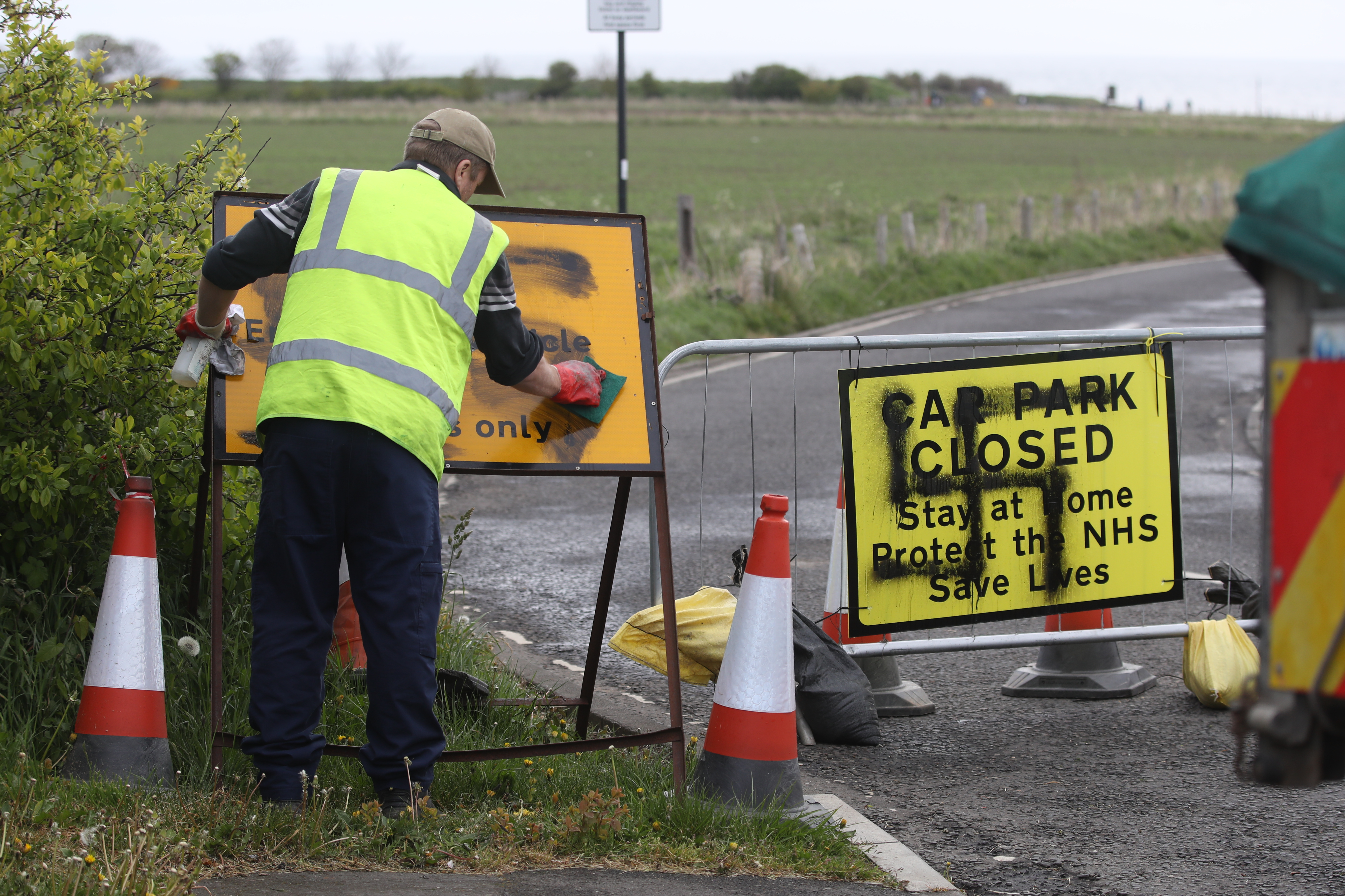 A worker removes a swastika spray painted on a sign at the entrance to a closed road and car park near Whitley Bay lighthouse, Northumberland. Graffiti has appeared on signs at several car parks along the Northumberland coastal road as the UK continues in lockdown to help curb the spread of the coronavirus.