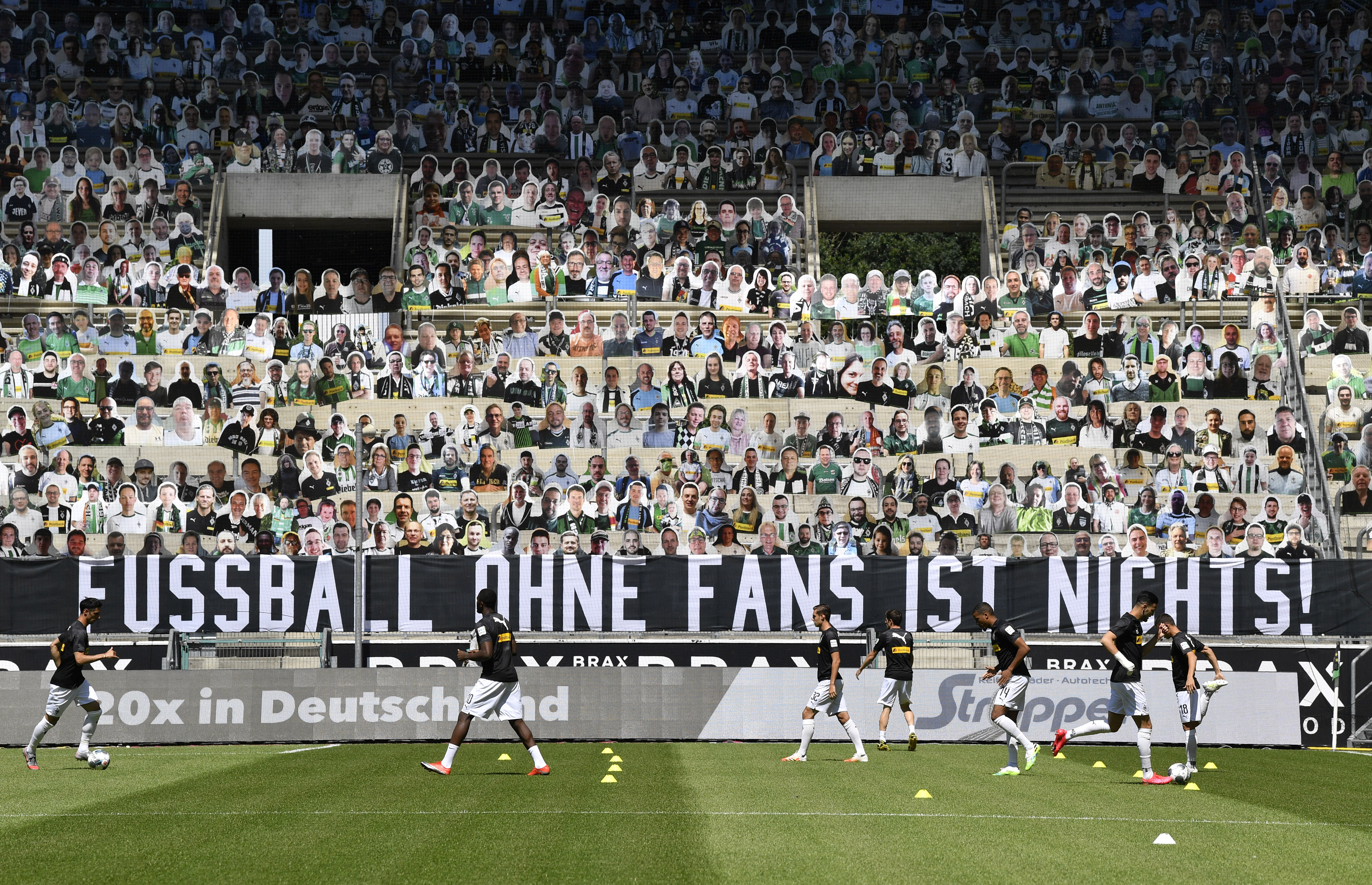 """Cardboards with photos of Moenchengladbach fans displayed on the stands during warm up prior the German Bundesliga soccer match between Borussia Moenchengladbach and Union Berlin in Moenchengladbach, Germany, Sunday, May 31, 2020. A banner reads: """"For Borussia. Against ghost games!"""". The German Bundesliga becomes the world's first major soccer league to resume after a two-month suspension because of the coronavirus pandemic. (AP Photo/Martin Meissner, Pool)"""