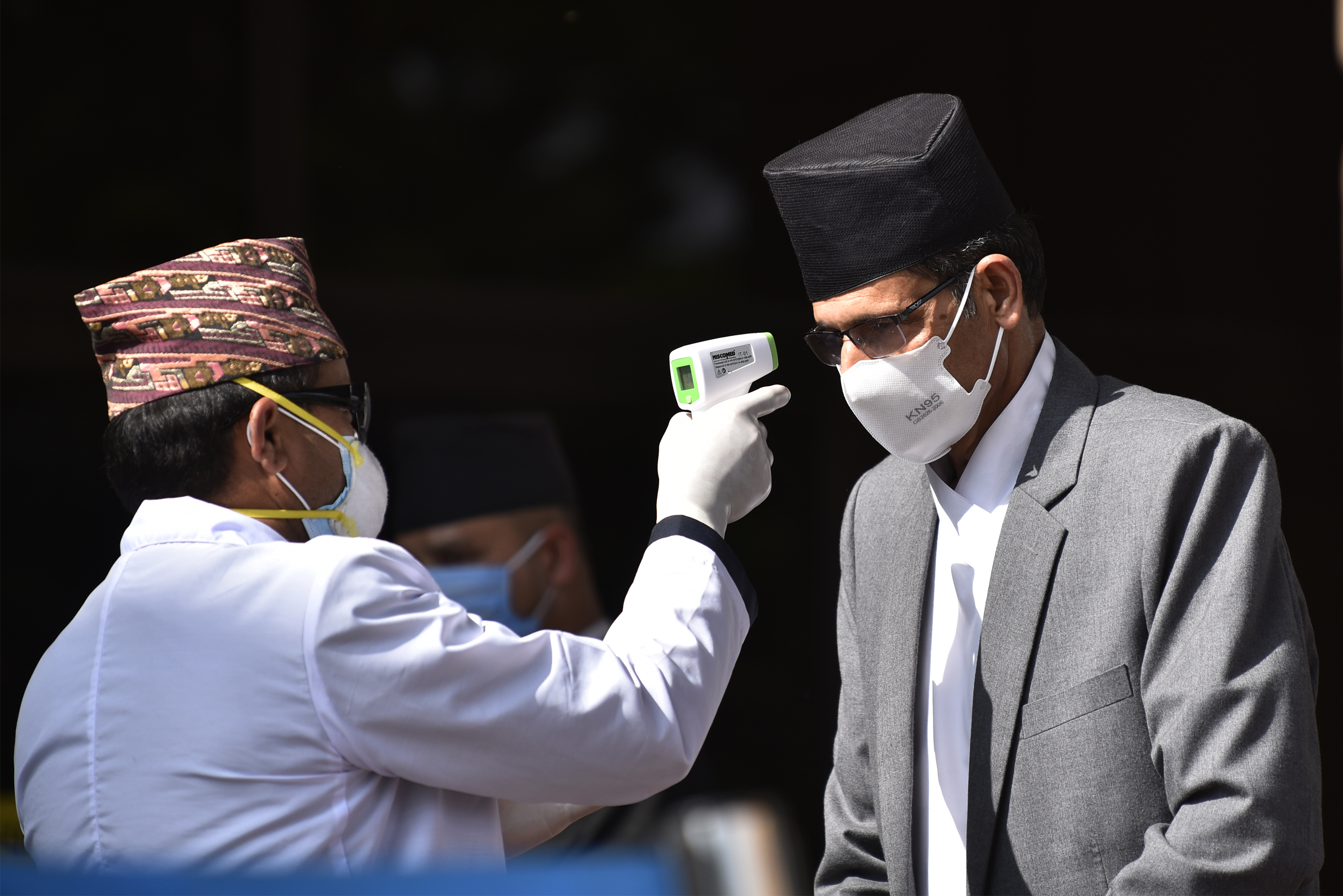 A Nepalese Health personnel in protective gear check the body temperature of Speaker of the House of Representatives, Agni Prasad Sapkota using thermal gun during the announcement of the new government's budget for the fiscal year 2020/2021 at Federal Parliament, Kathmandu, Nepal on Thursday, May 28, 2020. (Photo by Narayan Maharjan/NurPhoto via Getty Images)