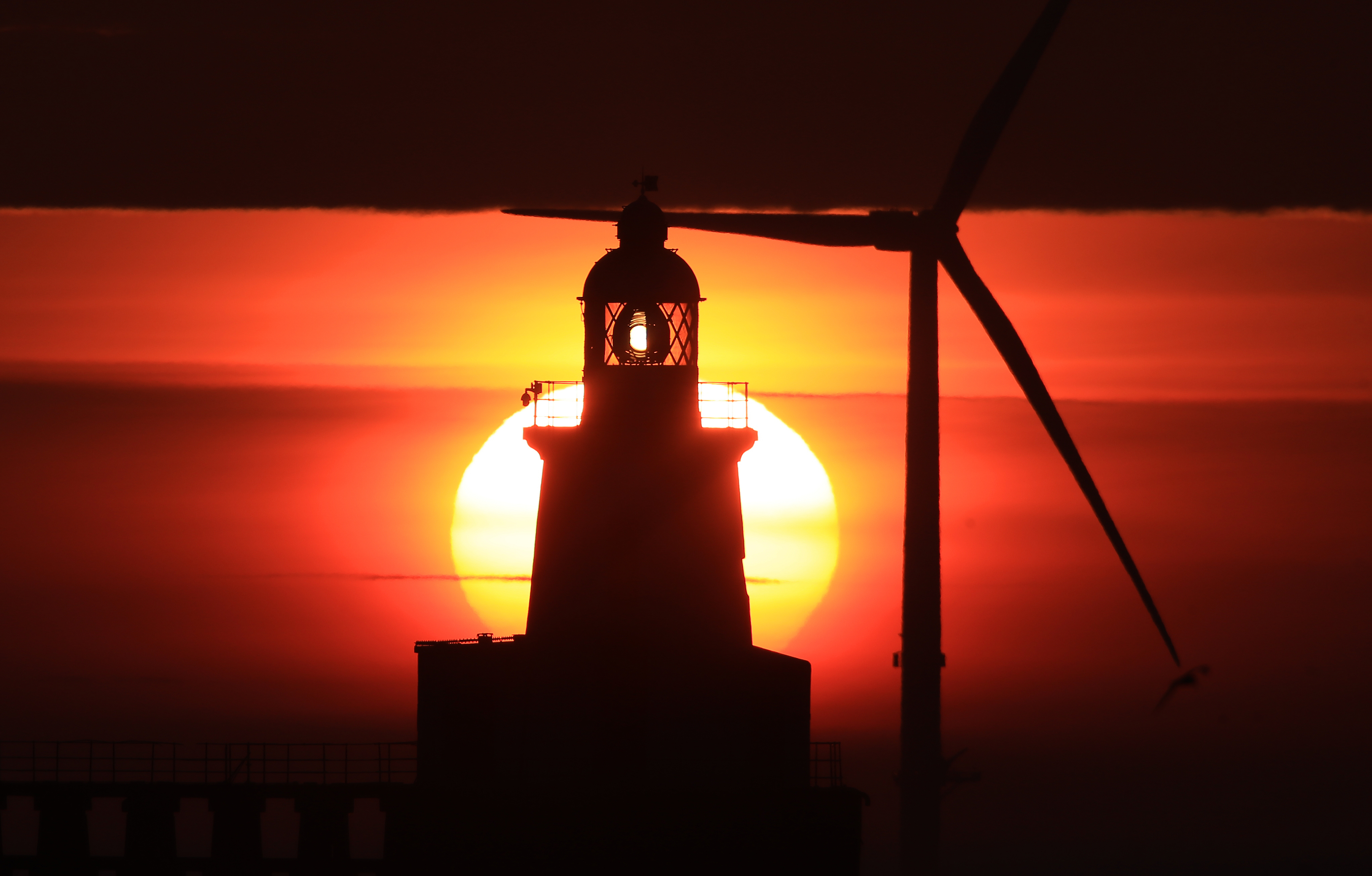 Sunrise at Blyth pier in Northumberland on the north east coast as the Met Office has predicted the hottest day of the year so far with temperatures set to hit 28C in some parts of the country. (Photo by Owen Humphreys/PA Images via Getty Images)