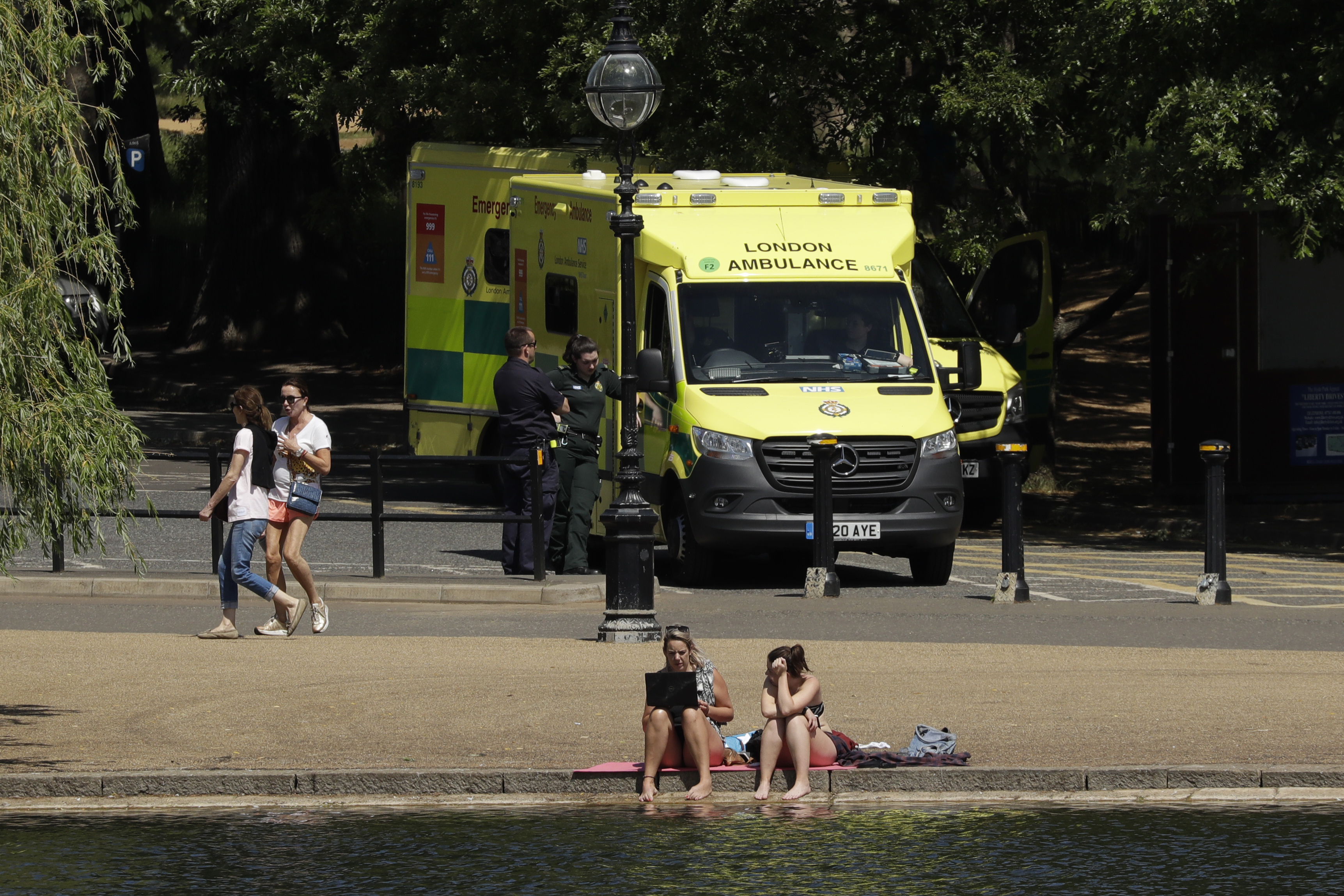 Two ambulances stand parked in a car park as people relax during warm weather by the Serpentine lake, in Hyde Park, London, Wednesday, May 20, 2020. Lockdown restrictions due to the coronavirus outbreak have been relaxed allowing unlimited outdoor exercise and activities such as sunbathing. The UK's Met Office said Wednesday, it is the hottest day of the year so far with 27.8 Celsius recorded at Heathrow. (AP Photo/Matt Dunham)