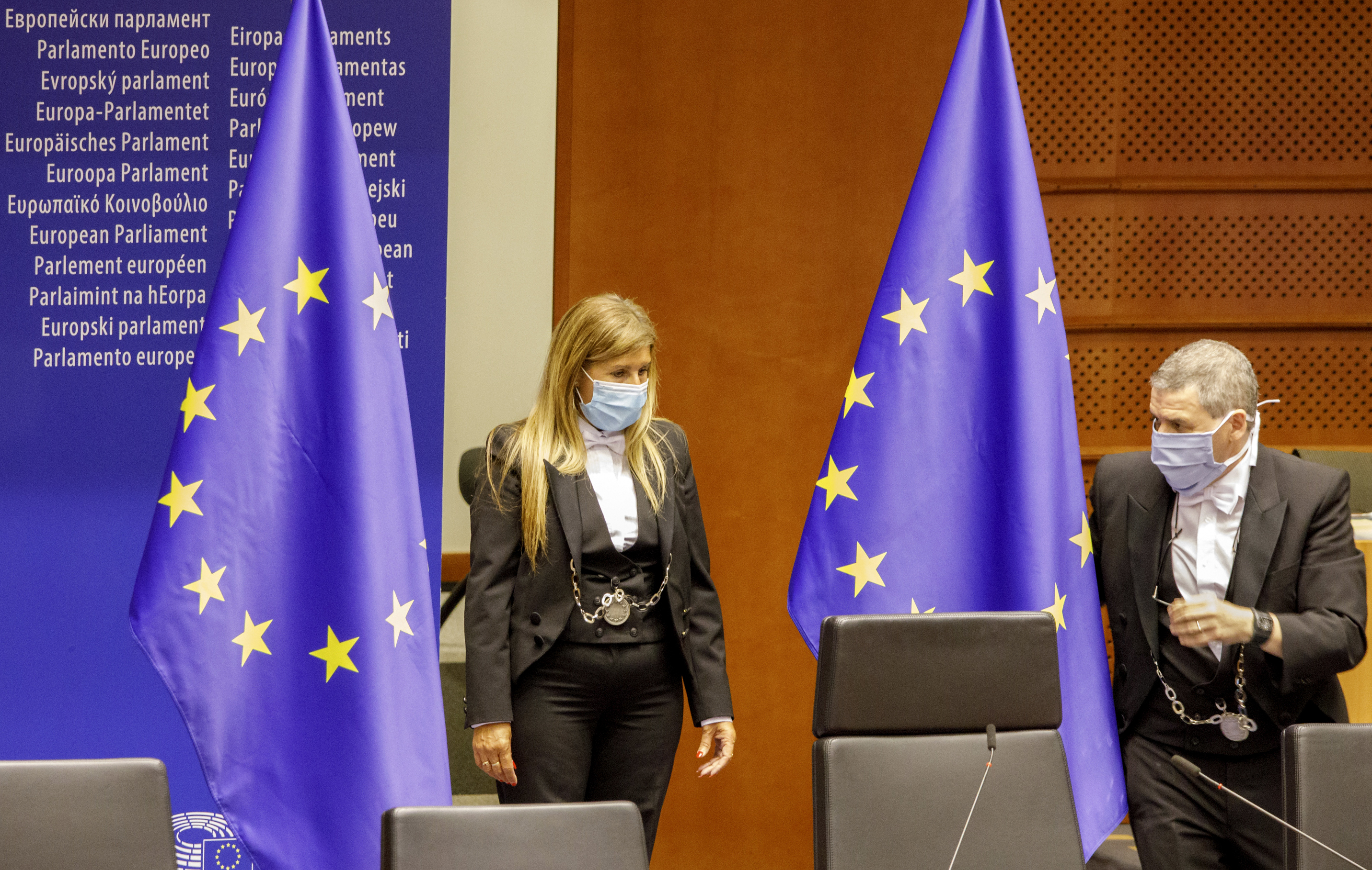 Two employees wear face masks, to prevent against the spread of coronavirus, as they prepare the plenary room at the European Parliament in Brussels, Wednesday, May 27, 2020. The European Union is to unveil Wednesday a massive coronavirus recovery plan worth hundreds of billions of euros to help countries rebuild their ailing economies, but the bloc remains deeply divided over what conditions should be attached to the funds. (AP Photo/Olivier Matthys)