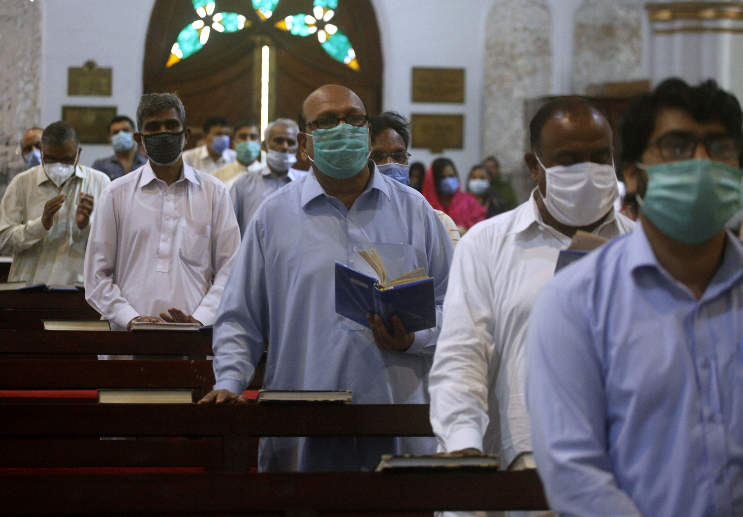 Christians wearing face masks to help curb the spread of the coronavirus attend Sunday Mass at Cathedral Church in Peshawar, Pakistan, Sunday, May 31, 2020. (AP Photo/Muhammad Sajjad)