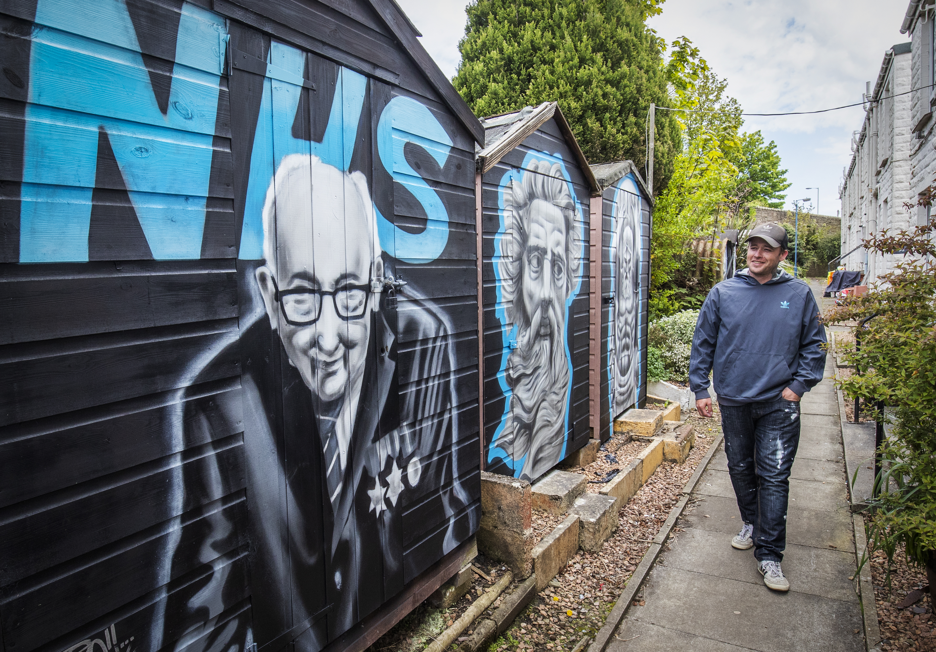 Artist Symon Mathieson alongside the mural he painted in tribute to Captain Tom and the NHS on a garden shed in Dundee centre, as the UK continues in lockdown to help curb the spread of the coronavirus.