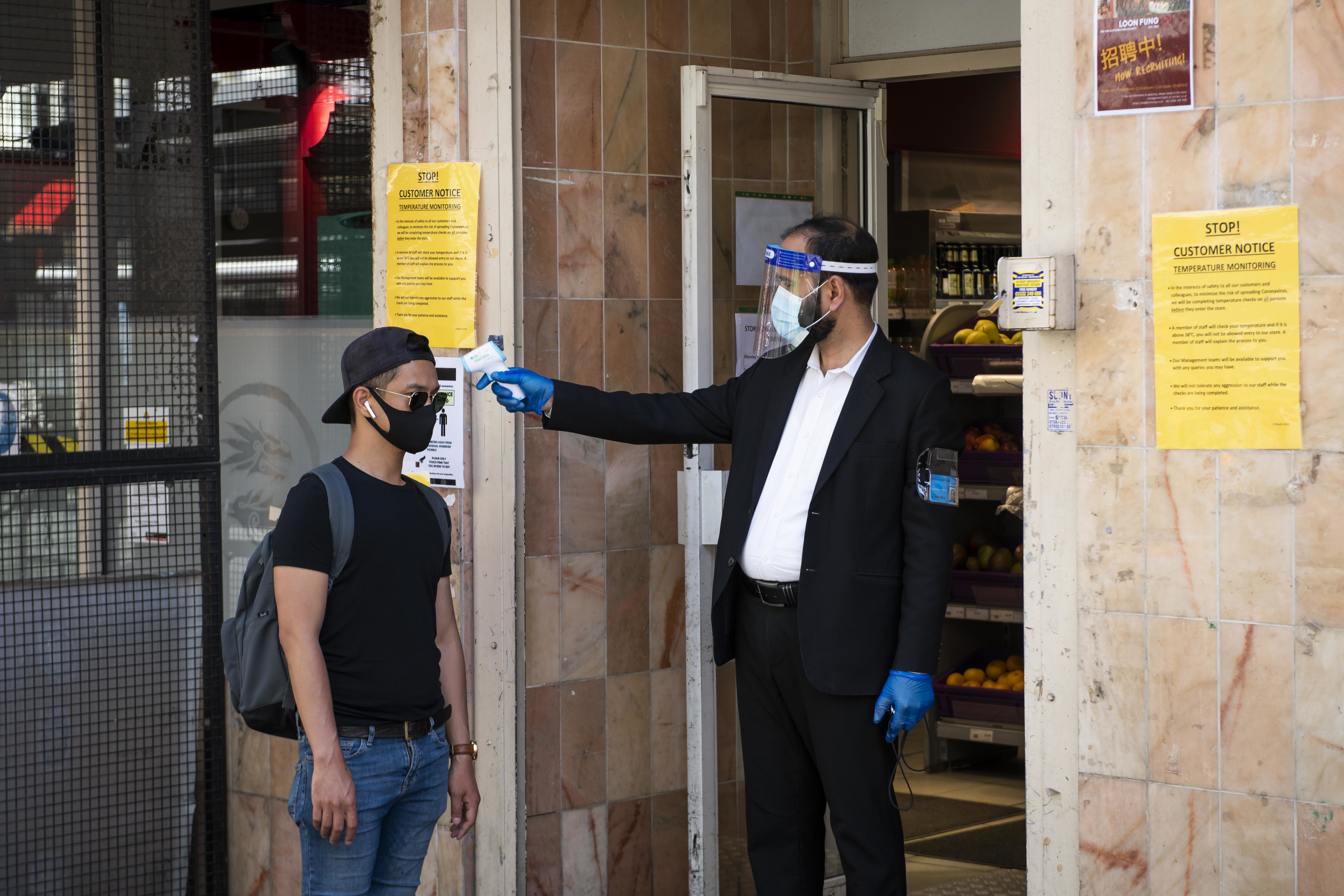 A security guard wearing a face shield and mask checks a customers temperature before he enters a supermarket, as the Coronavirus pandemic lockdown eases, Chinatown, London. Picture date: Friday 29th May 2020. Photo credit should read: David Jensen/EMPICS Entertainment