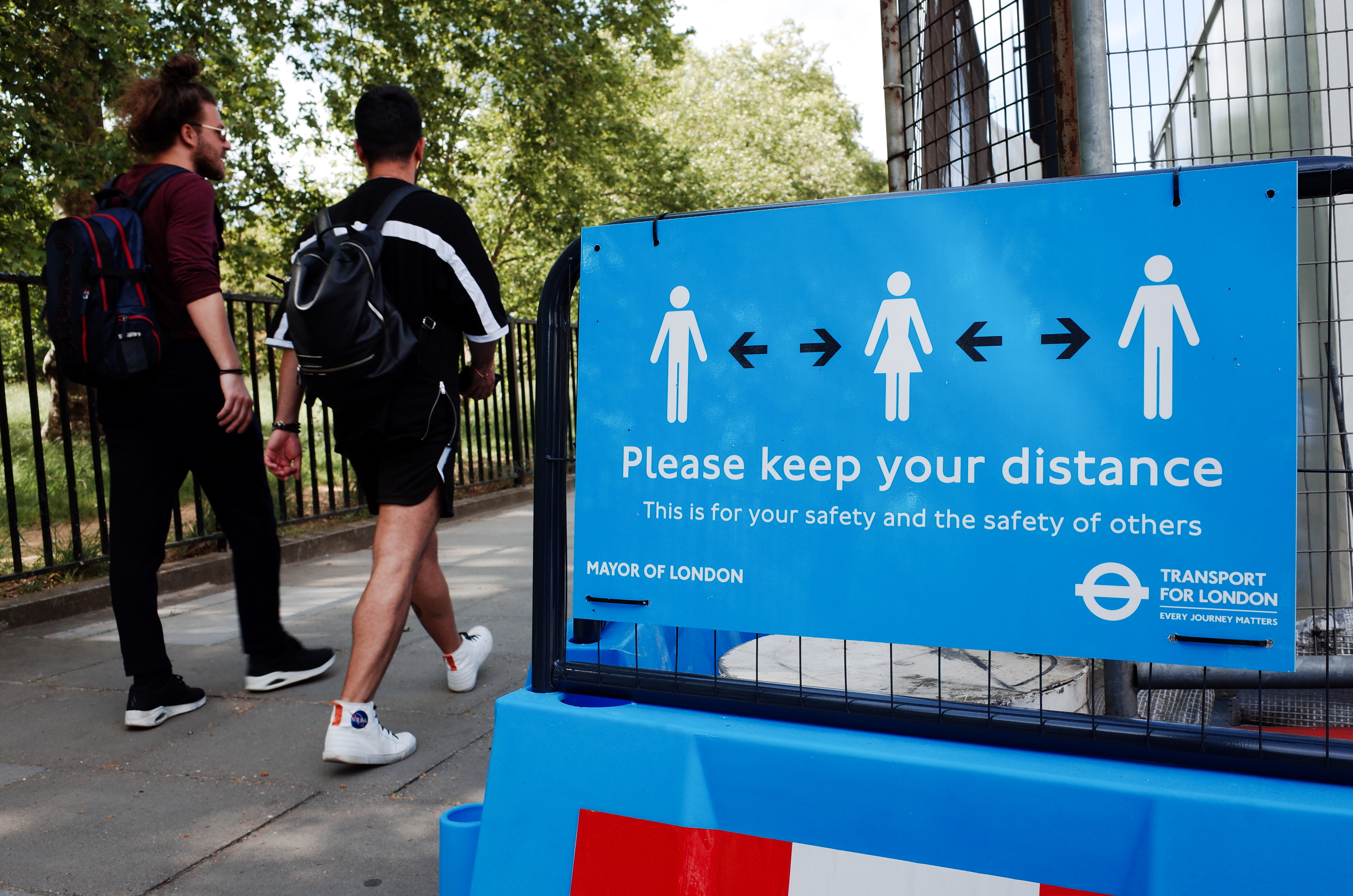 Two men walk past a sign reminding people to observe social distancing on Park Lane in London, England, on May 18, 2020. Britain began its ninth week of coronavirus lockdown today, a day after the lowest reported covid-19 death toll (170) across the country since March. A day of even lower covid-19 fatalities today (160) is meanwhile cementing hopes that the UK is firmly into the recovery phase of its coronavirus crisis, and that its continued emergence from lockdown will be able to carry on as planned. (Photo by David Cliff/NurPhoto via Getty Images)