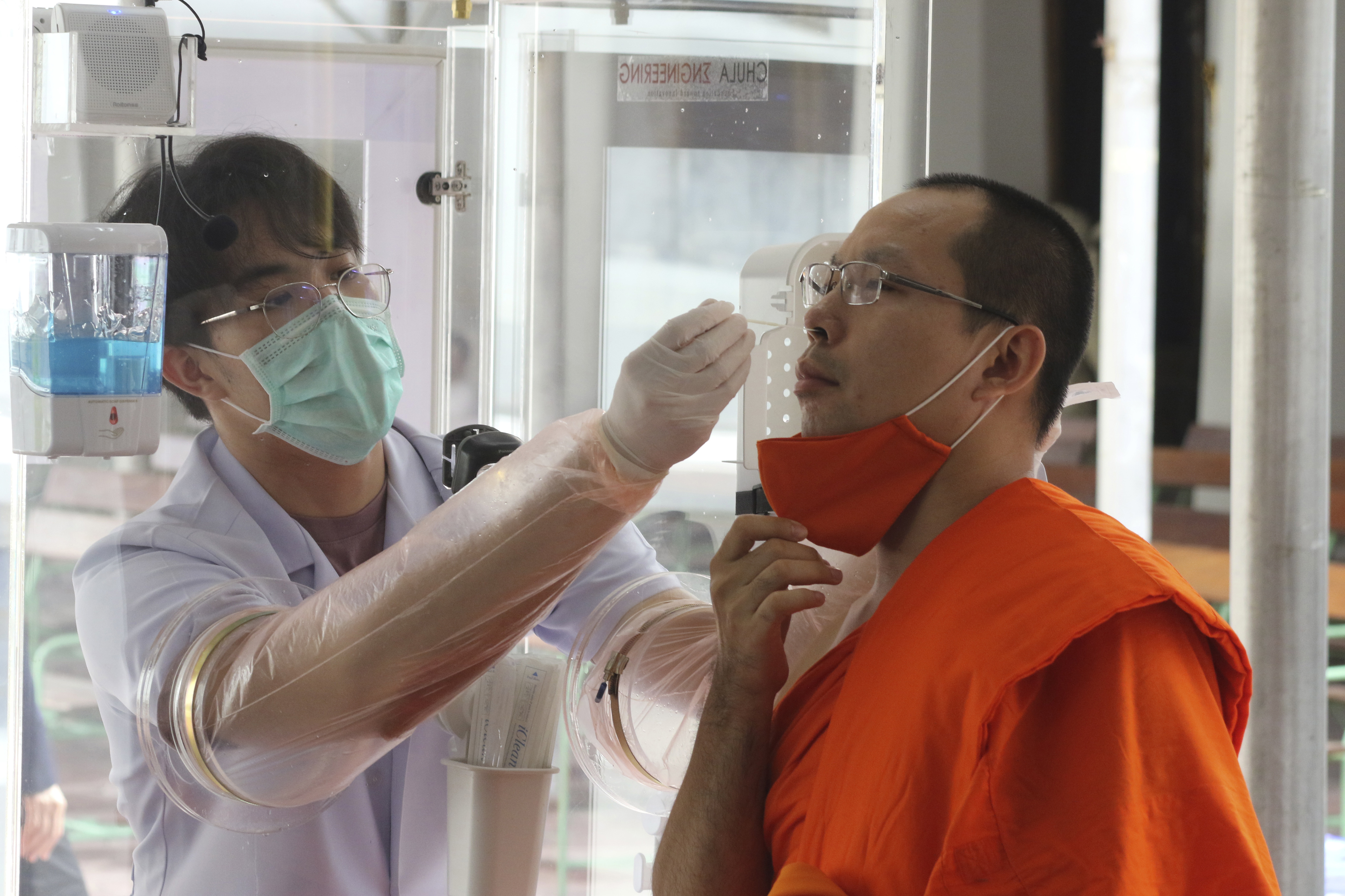 Health workers collect a nasal swab sample from a Buddhist monk to test for the coronavirus at the Wat Pho temple in Bangkok, Thailand, Saturday, May 30, 2020. (AP Photo/Sarayuth Jojaiharn))