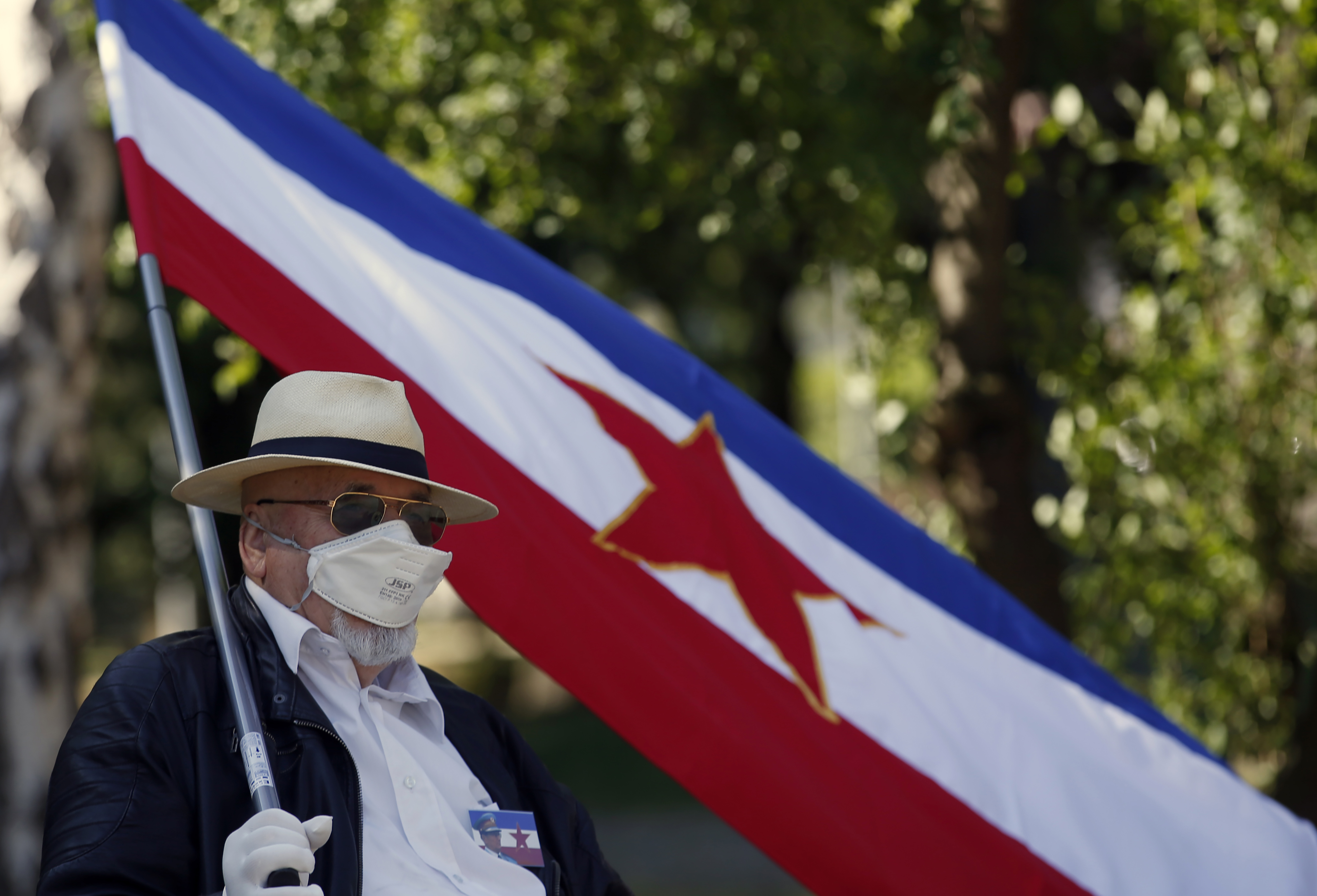 A supporter of the late Yugoslav communist president Josip Broz Tito wearing a mask to protect against coronavirus holds an old Yugoslav flag with the communist five-point star in front of memorial complex prior to a wreath laying ceremony in Belgrade, Serbia, Monday, May 25, 2020. People flocked to Tito's grave to mark the 128th anniversary of his birth. (AP Photo/Darko Vojinovic)