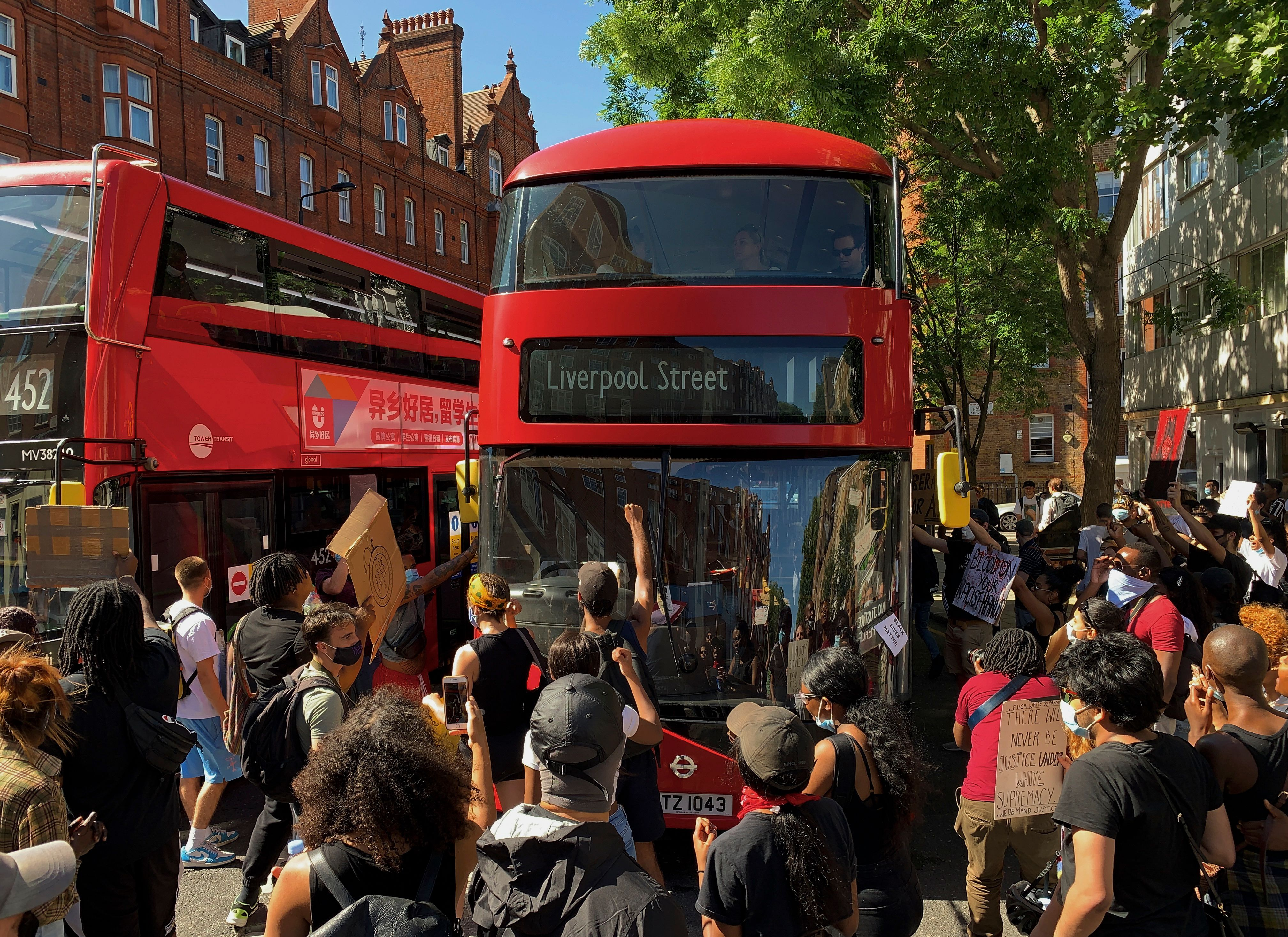 Demonstrators stop a bus as they block the street in Sloane Square in London on May 31, 2020 after marching on the US embassy to protest the death of George Floyd, an unarmed black man who died after a police officer knelt on his neck for nearly nine minutes during an arrest in Minneapolis, USA. - Hundreds gathered in central London and marched to the US Embassy to protest the death of an unarmed black man in Minneapolis while in police custody that has sparked days of unrest in the US city and beyond. (Photo by DANIEL LEAL-OLIVAS / AFP) (Photo by DANIEL LEAL-OLIVAS/AFP via Getty Images)