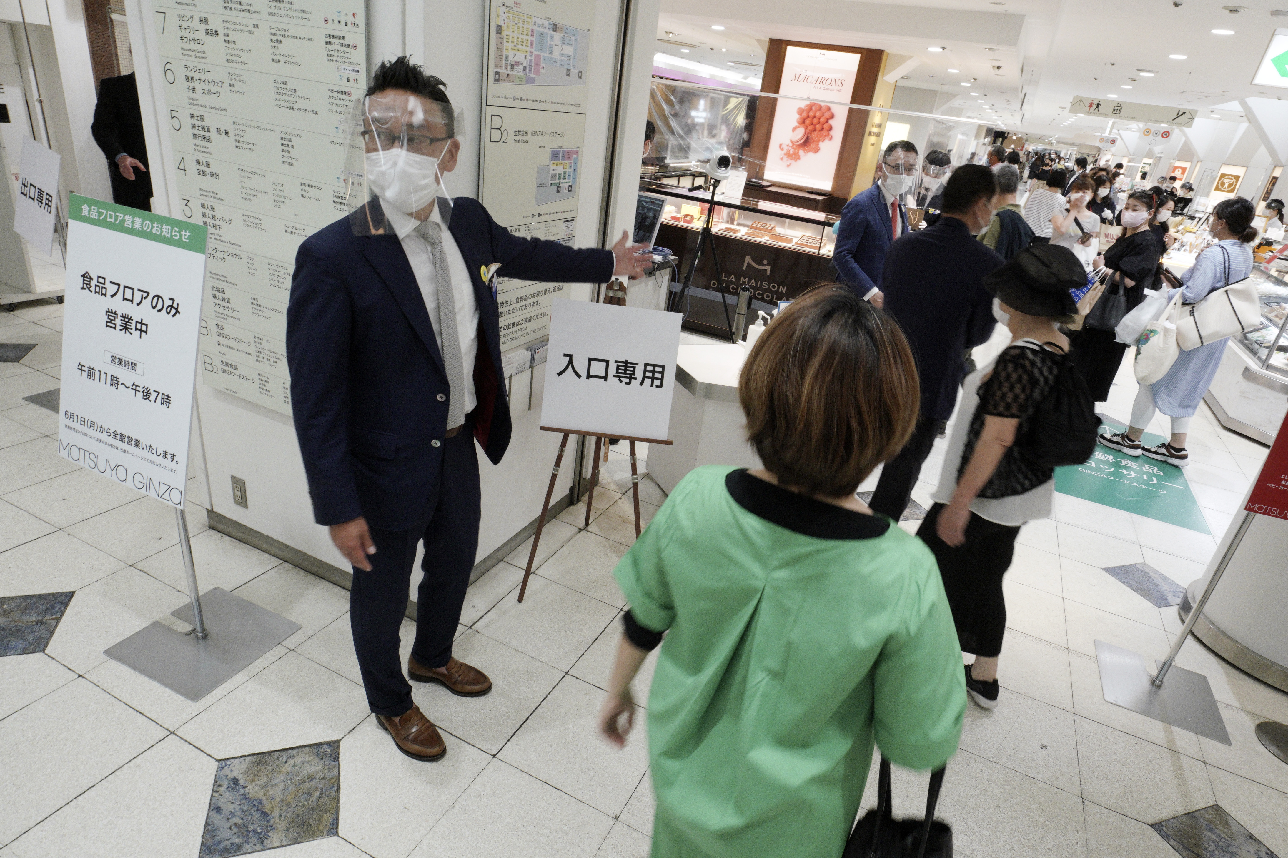 """Shoppers maintain a safe social distance between each other as they wait in line to enter a food section of the Matsuya Ginza department store which partially reopens Monday, May 25, 2020, in Tokyo. Japan's Prime Minister Shinzo Abe is expected to remove a coronavirus state of emergency from Tokyo and four other remaining prefectures later in the day. Japanese words read as """"For entrance only."""" (AP Photo/Eugene Hoshiko)"""