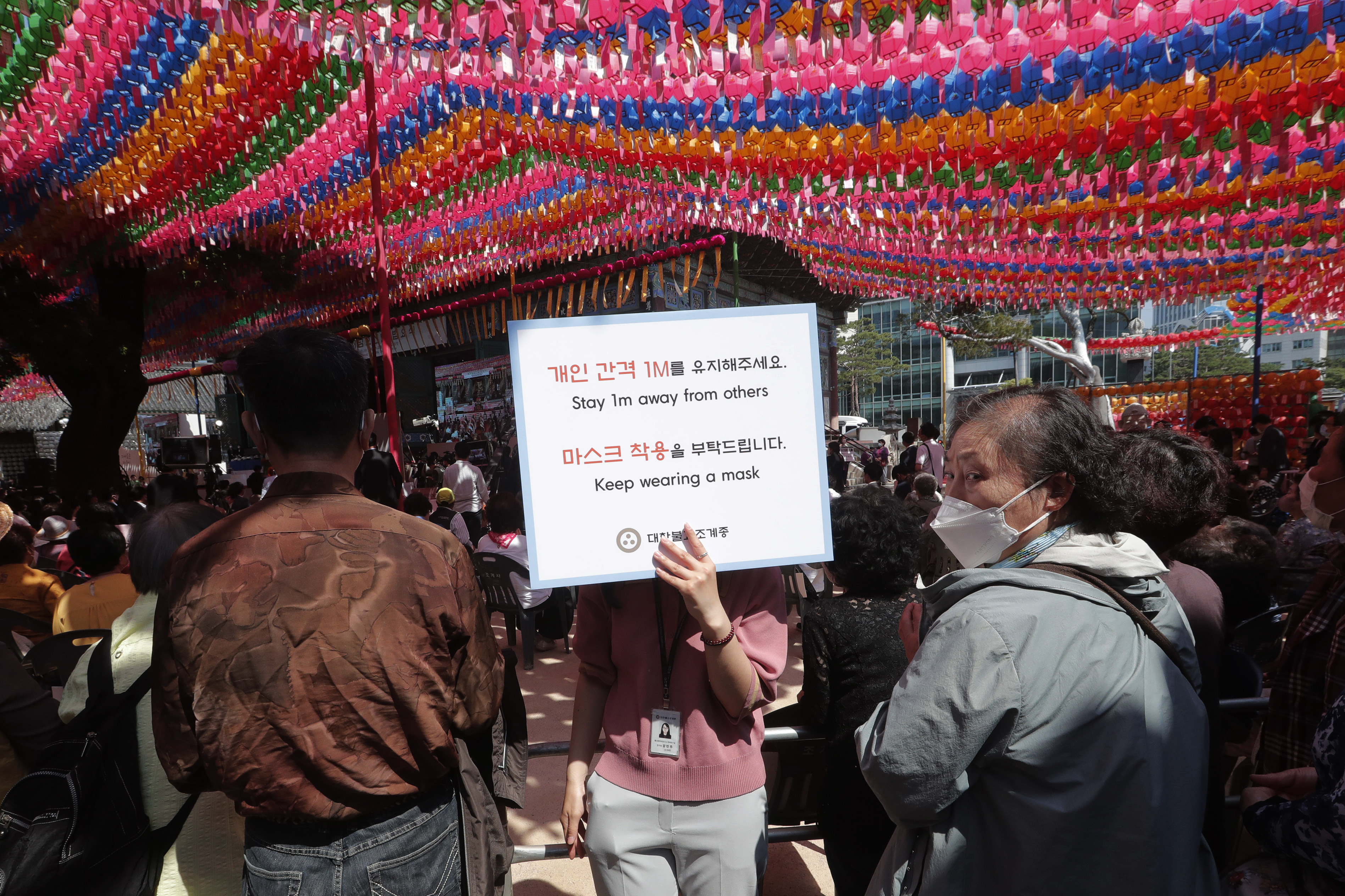 A Buddhist believer holds a notice about precautions against the new coronavirus during the Buddha's birthday ceremony at the Jogye temple in Seoul, South Korea, Saturday, May 30, 2020. This year a ceremony to celebrate the birth anniversary was put off from April 30 to May 30 due to the coronavirus. (AP Photo/Ahn Young-joon)