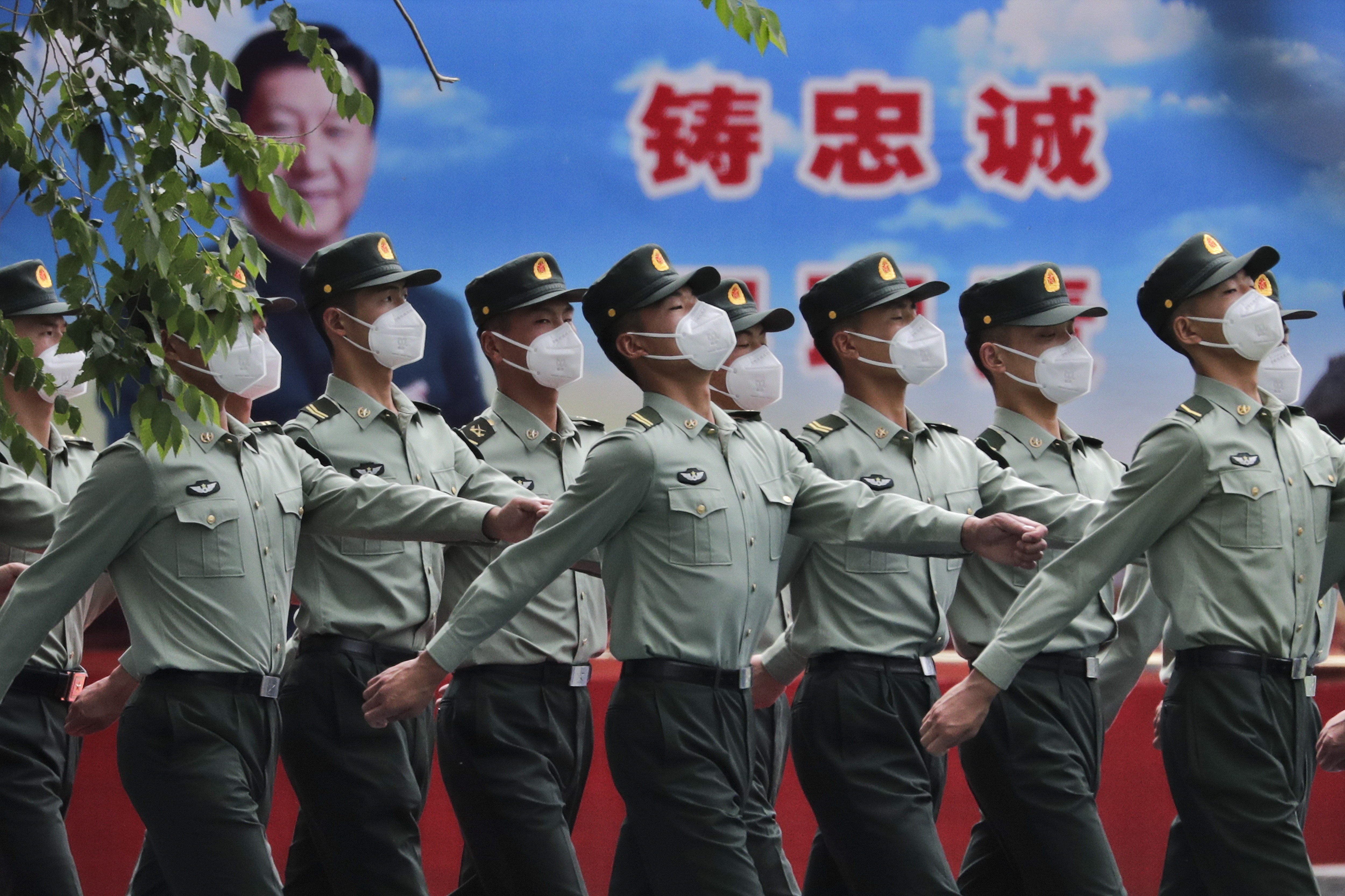 Chinese People's Liberation Army (PLA) soldiers wearing face masks to protect against the spread of the new coronavirus march past a banner depicting Chinese President Xi Jinping at their living squatter inside the Tiananmen Gate in Beijing during a plenary session of China's National People's Congress (NPC) at the Great Hall of the People in Beijing, Monday, May 25, 2020. (AP Photo/Andy Wong)