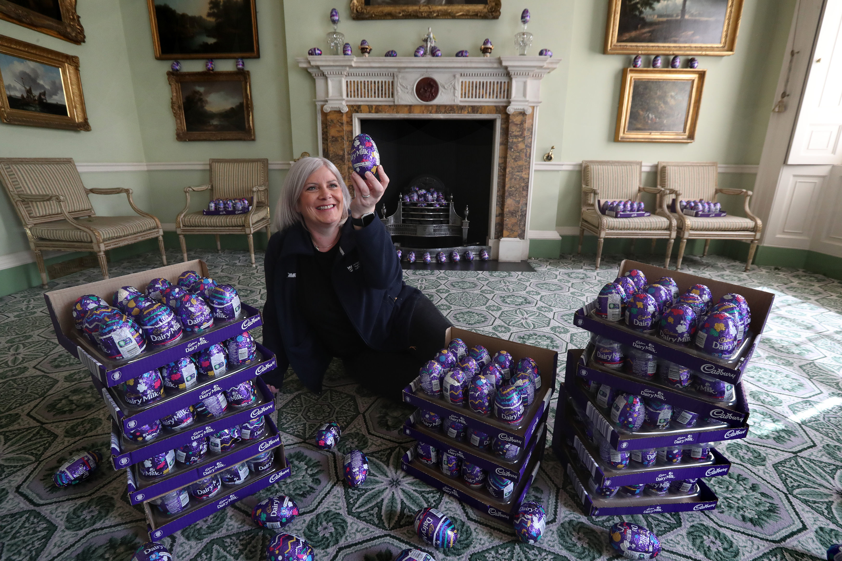Claire Grant from the National Trust for Scotland with a pile of Easter eggs in the Drawing Room at the National Trust's Georgian House in Edinburgh, as the Trust are trying to find homes for more than 15,000 chocolate eggs that are left over from Easter egg hunts that were cancelled at their properties around the UK due to the coronavirus lockdown.