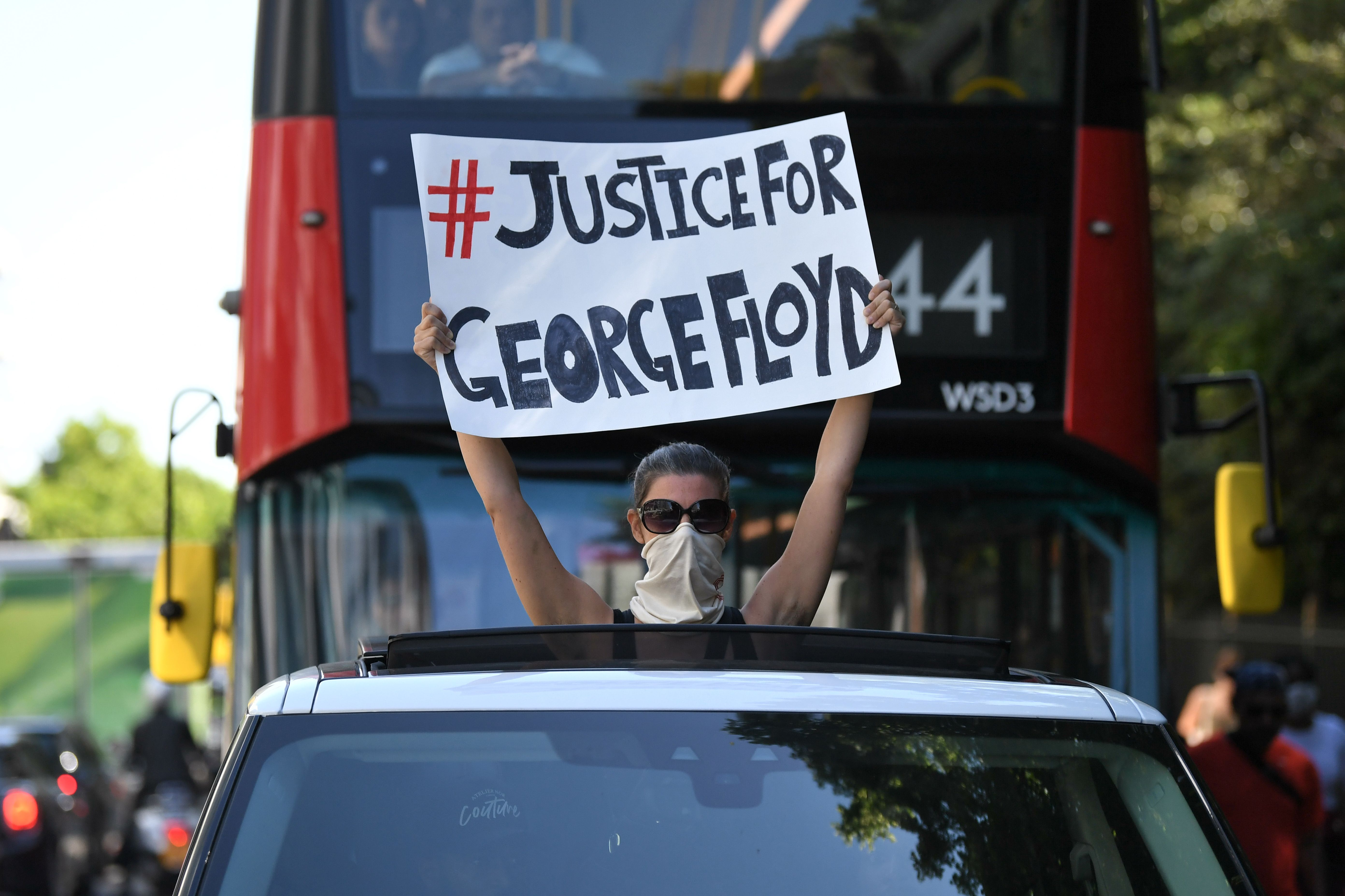 A woman holds a sign out of the sunroof of a car in central London on May 31, 2020 calling for justice following the death of George Floyd, an unarmed black man who died after a police officer knelt on his neck for nearly nine minutes during an arrest in Minneapolis, USA. - Hundreds gathered in central London and marched to teh US Embassy to protest the death of an unarmed black man in Minneapolis while in police custody that has sparked days of unrest in the US city and beyond. (Photo by DANIEL LEAL-OLIVAS / AFP) (Photo by DANIEL LEAL-OLIVAS/AFP via Getty Images)