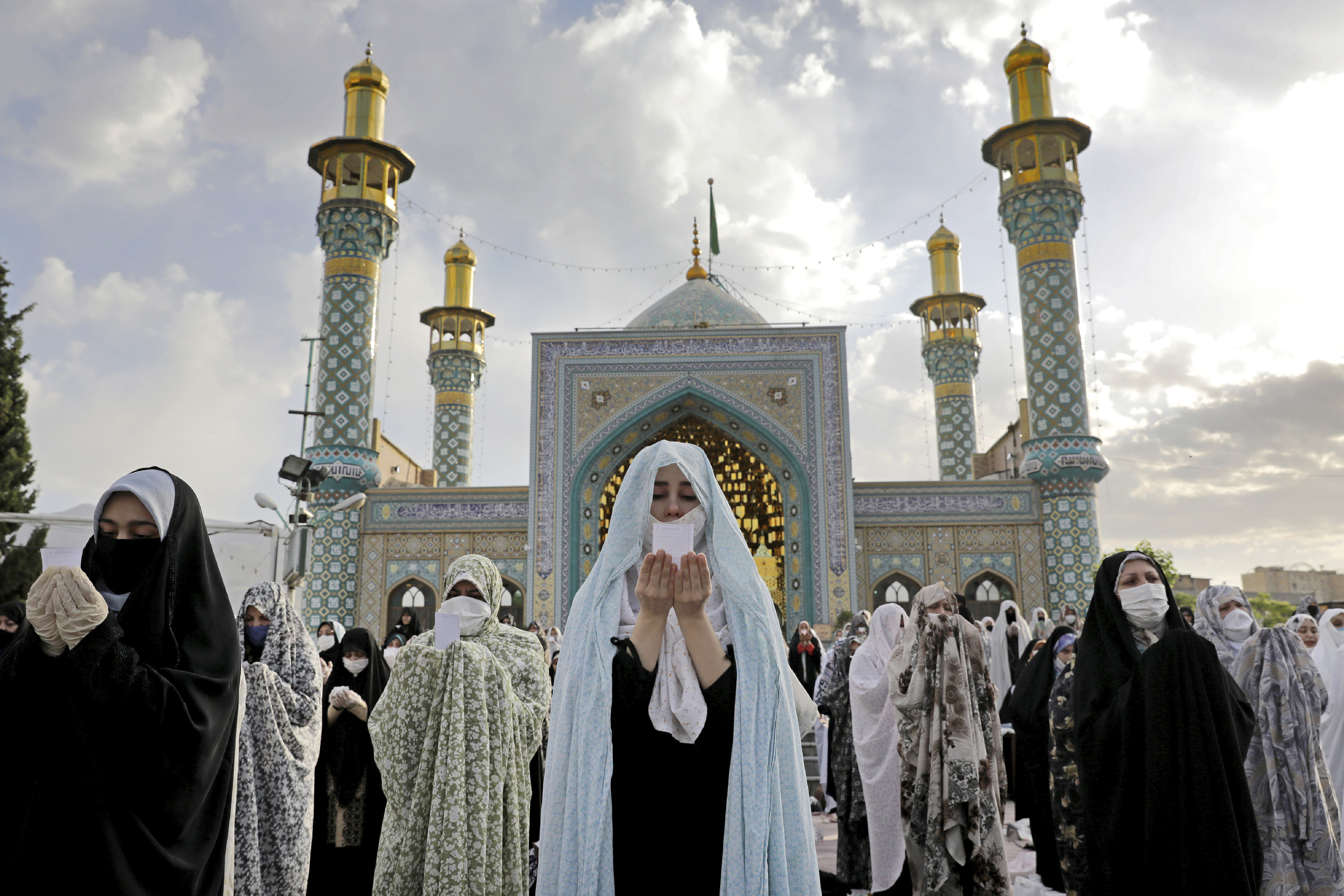 Worshippers wearing protective face masks offer Eid al-Fitr prayers outside a shrine to help prevent the spread of the coronavirus, in Tehran, Iran, Sunday, May 24, 2020. Muslims worldwide celebrate one of their biggest holidays under the long shadow of the coronavirus, with millions confined to their homes and others gripped by economic concerns during what is usually a festive time of shopping and celebration. (AP Photo/Ebrahim Noroozi)