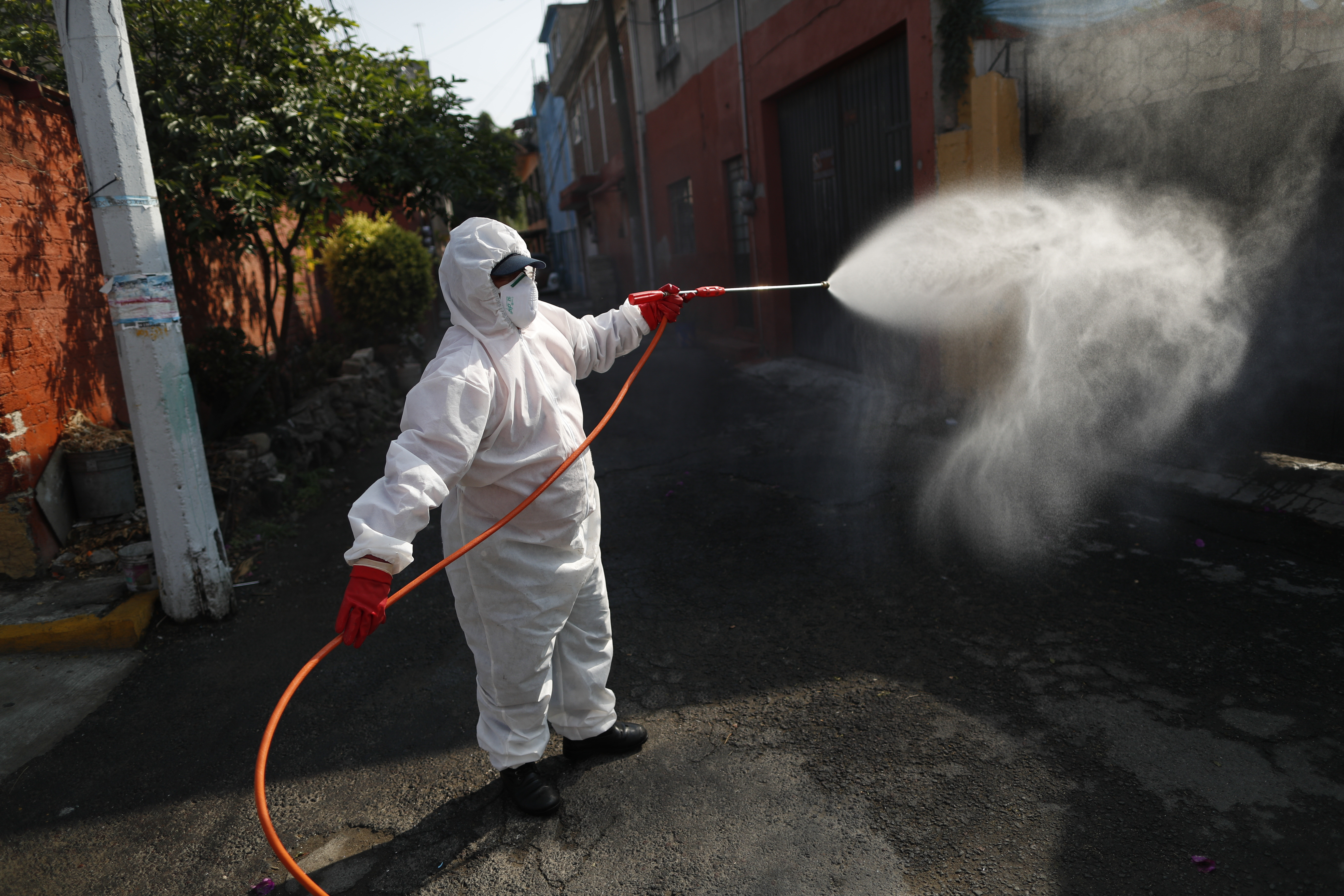 A public safety worker sprays a disinfectant solution in the streets of the El Rosario neighborhood, which had seen a recent cluster of COVID-19 cases, in Xochimilco, Mexico City, Mexico, Friday, May 29, 2020. (AP Photo/Rebecca Blackwell)