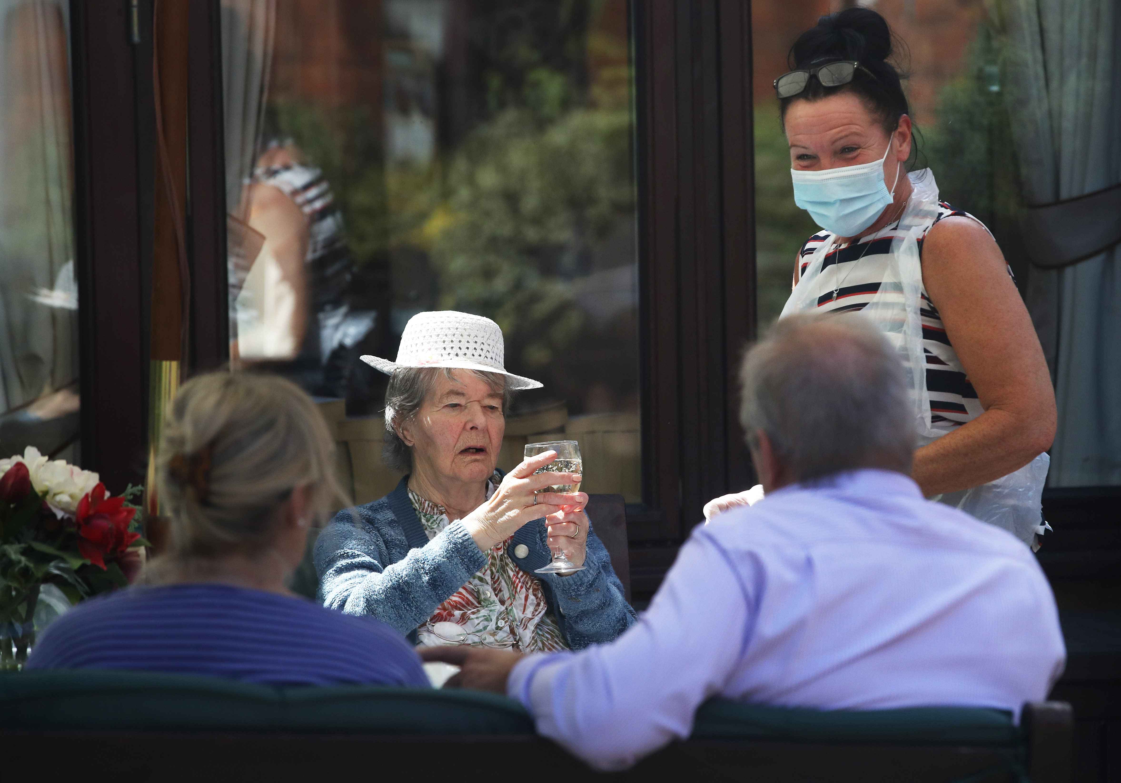 Margaret Yeoman, 90, sees her son John Yeoman, 62, and his wife Denise Yeoman, 63, for the first time in eight weeks as they visit her at the Eothen Homes care home in Whitley Bay, Tyneside, their first in person contact since lockdown began. (Photo by Owen Humphreys/PA Images via Getty Images)