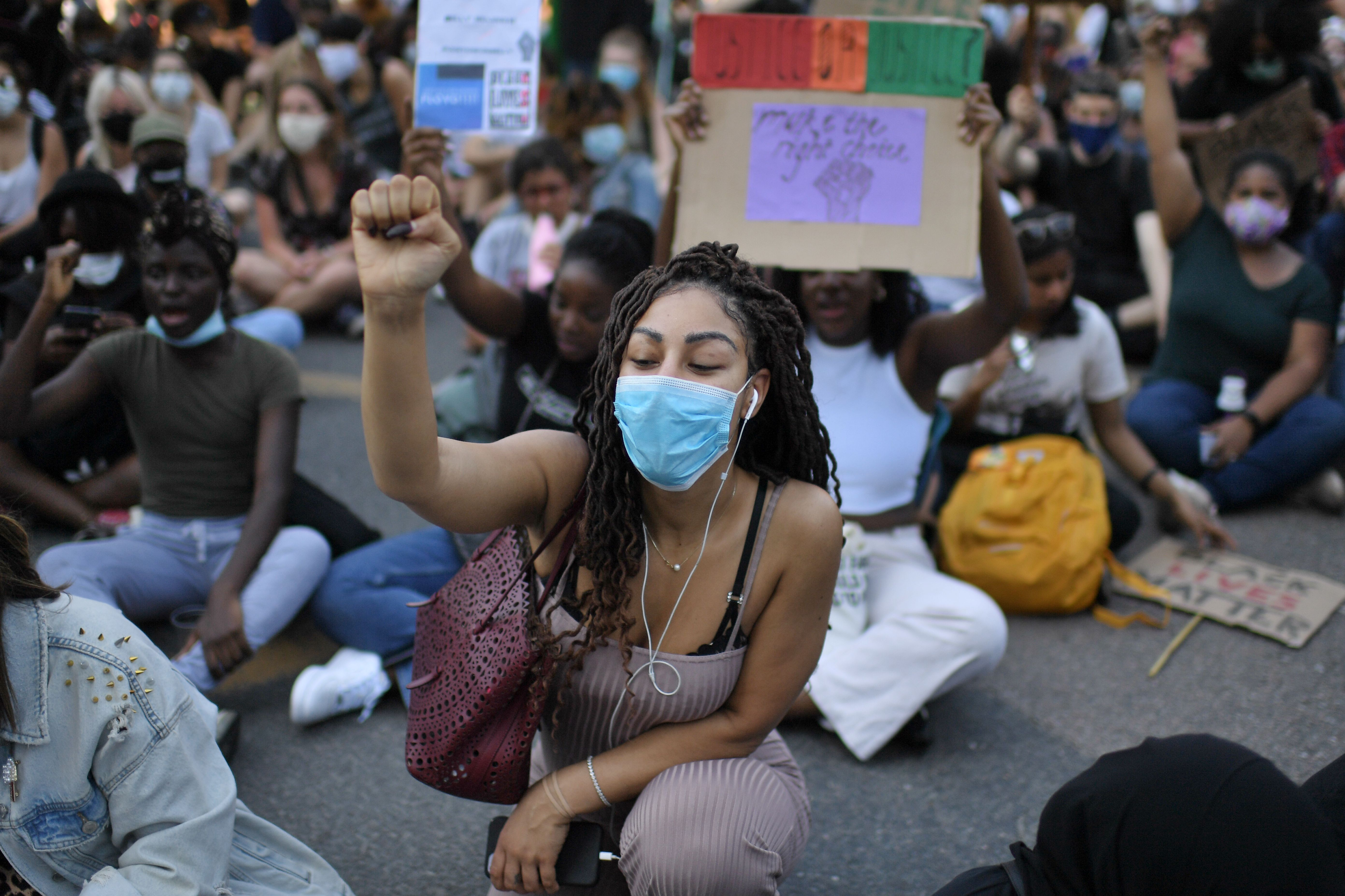 Demonstrators sit down in the road outside the US Embassy in London on May 31, 2020 to protest the death of George Floyd, an unarmed black man who died after a police officer knelt on his neck for nearly nine minutes during an arrest in Minneapolis, USA. - Hundreds gathered in central London and marched to teh US Embassy to protest the death of an unarmed black man in Minneapolis while in police custody that has sparked days of unrest in the US city and beyond. (Photo by DANIEL LEAL-OLIVAS / AFP) / The erroneous mention[s] appearing in the metadata of this photo by DANIEL LEAL-OLIVAS has been modified in AFP systems in the following manner: [London] instead of [Brighton]. Please immediately remove the erroneous mention[s] from all your online services and delete it (them) from your servers. If you have been authorized by AFP to distribute it (them) to third parties, please ensure that the same actions are carried out by them. Failure to promptly comply with these instructions will entail liability on your part for any continued or post notification usage. Therefore we thank you very much for all your attention and prompt action. We are sorry for the inconvenience this notification may cause and remain at your disposal for any further information you may require. (Photo by DANIEL LEAL-OLIVAS/AFP via Getty Images)